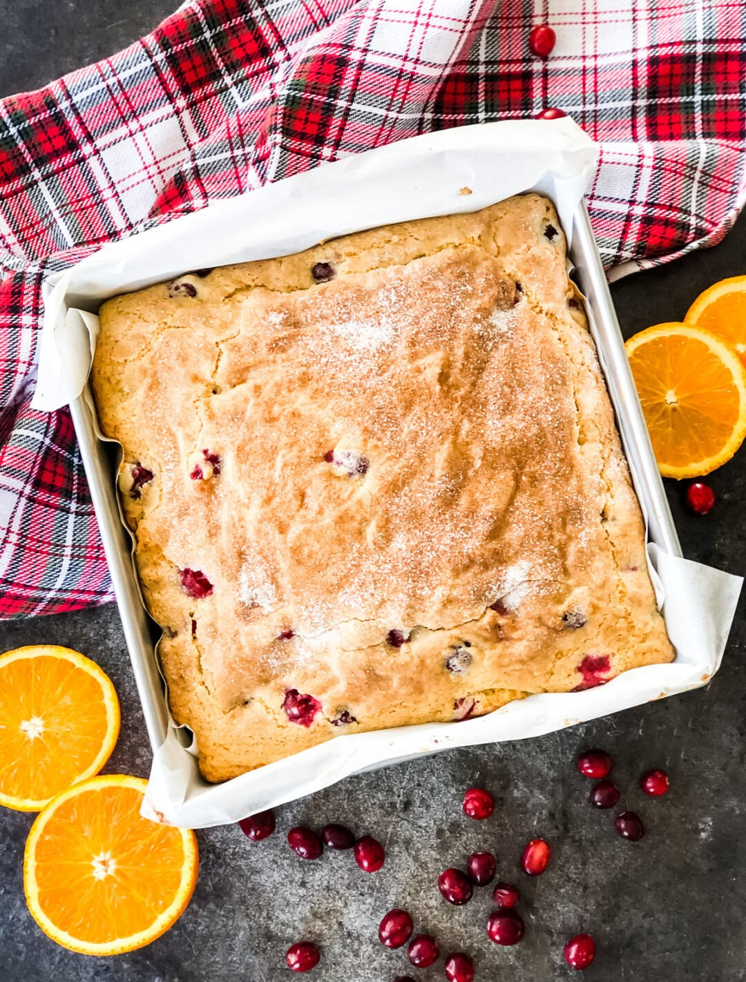 A top down view of a Cranberry Orange Buttermilk Breakfast Cake on a table with a plaid napkin and orange slices