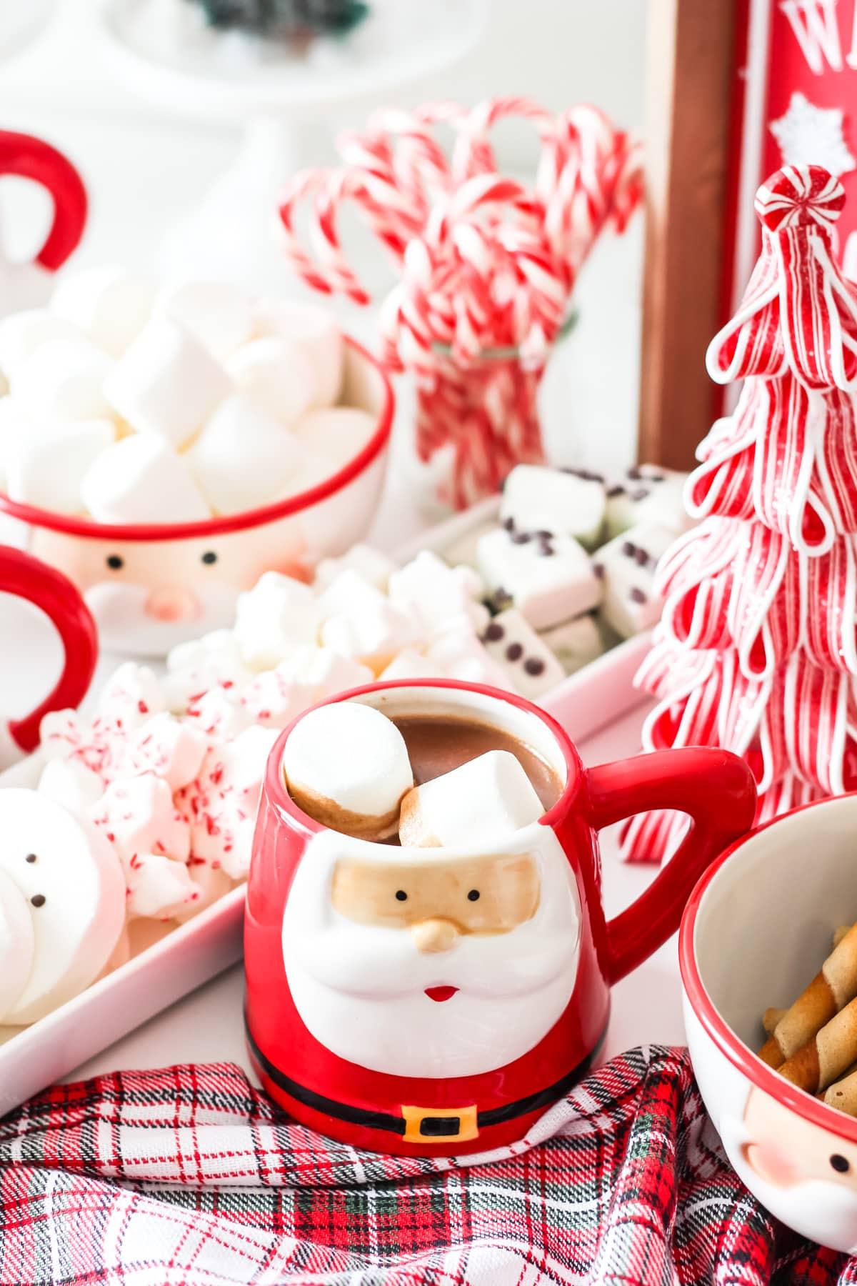 A Santa mug full of hot chocolate and marshmallows sitting on a table of Christmas treats