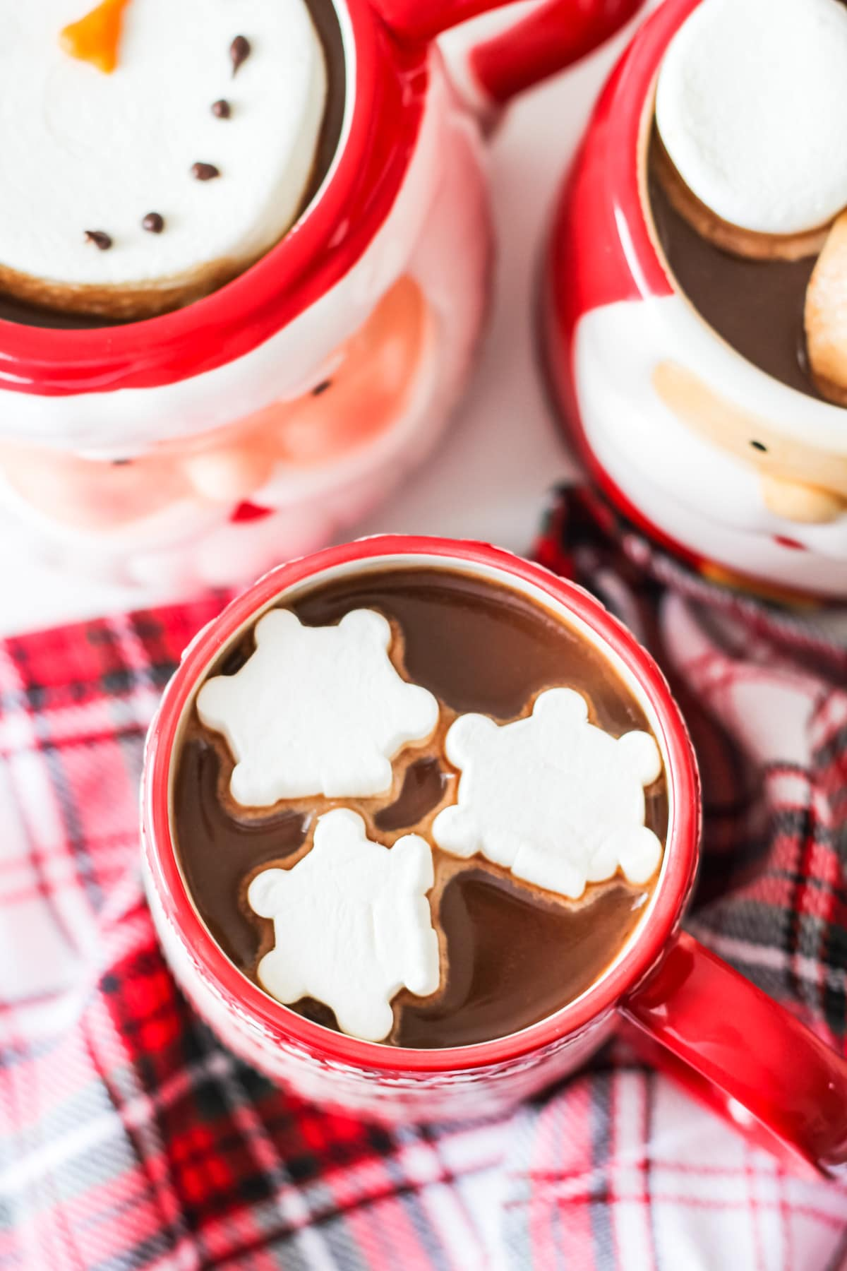 A top down view of a mug of hot chocolate with snowflake marshmallows