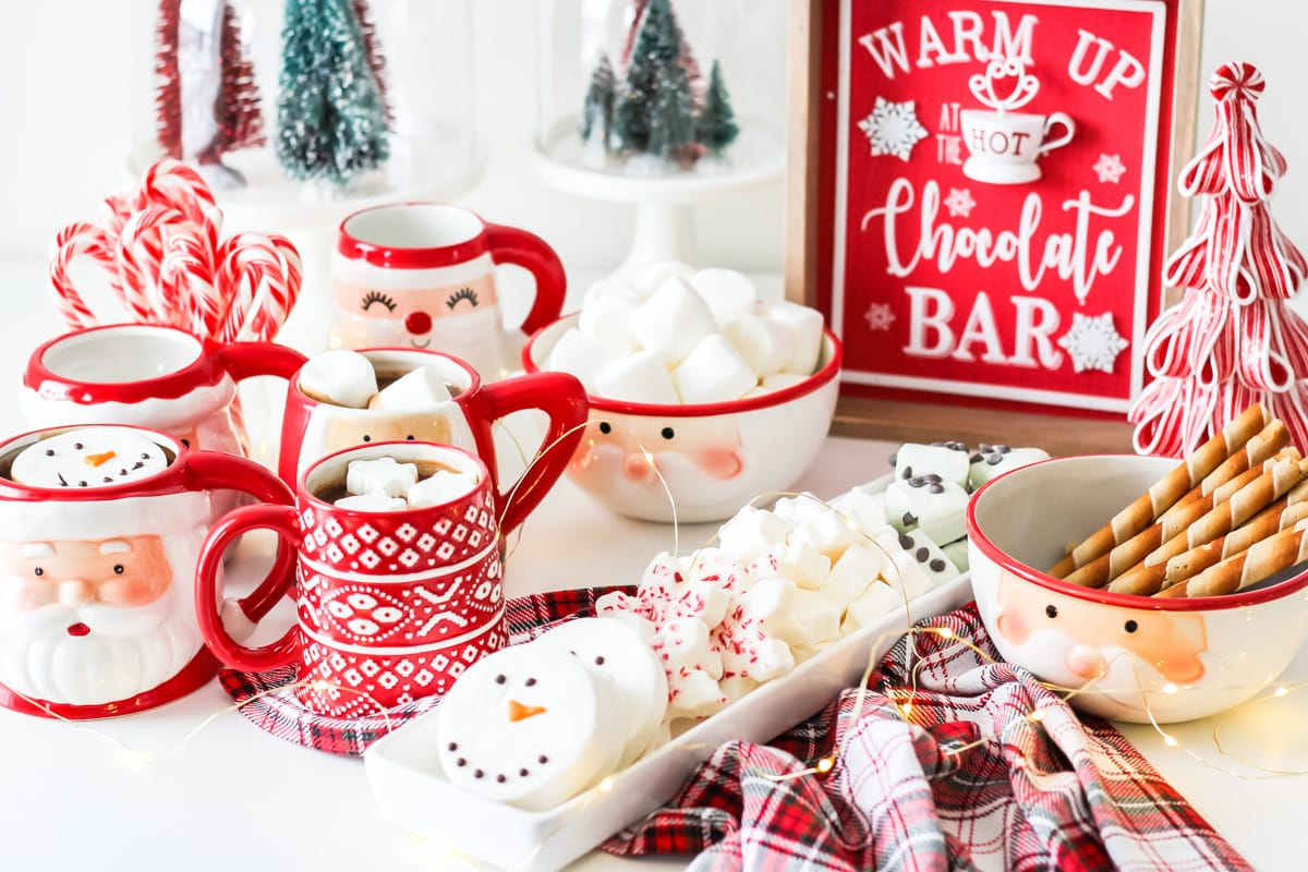 A table full of Santa mugs, marshmallows and candy canes