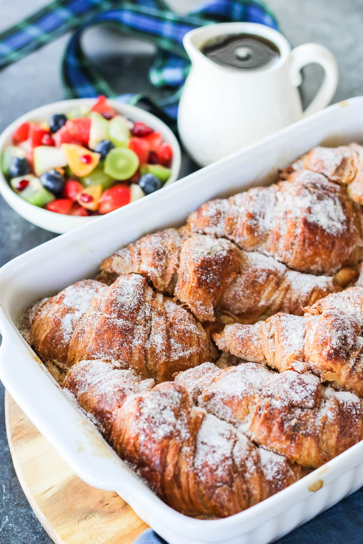 a close up view of a Croissant French Toast Bake covered in sugar. A bowl of fruit salad and syrup in the background