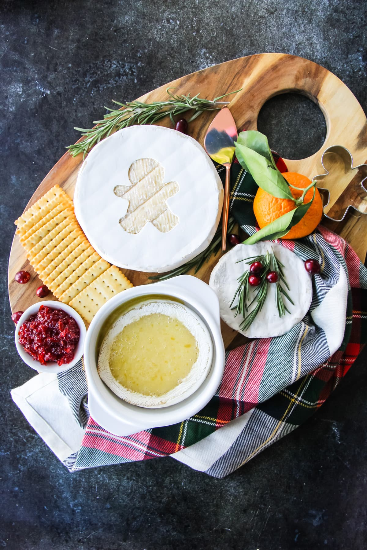 A cheese board with a baked Brie fondue, a wheel of Brie cheese with a gingerbread cut out and a small Brie topped with fresh rosemary and cranberries