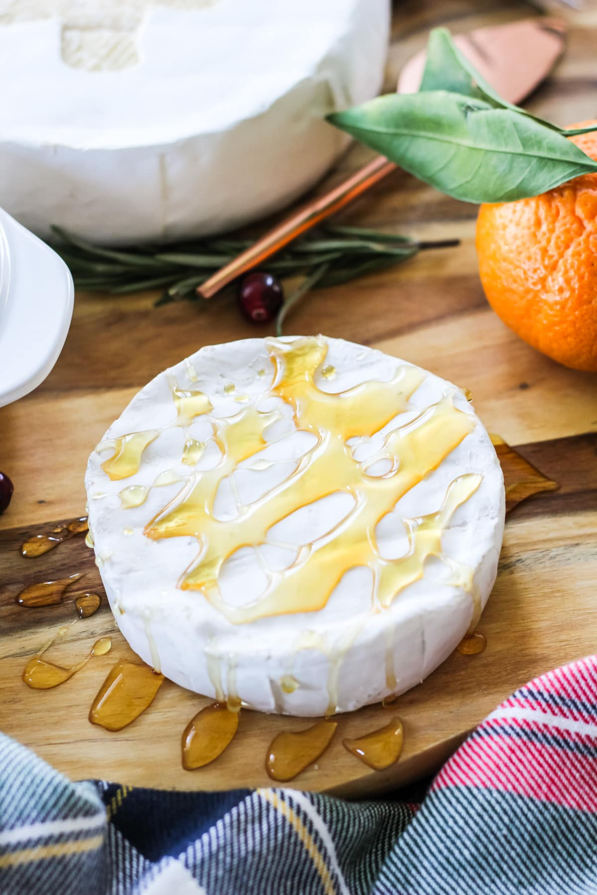 A wheel of Brie cheese drizzled with honey