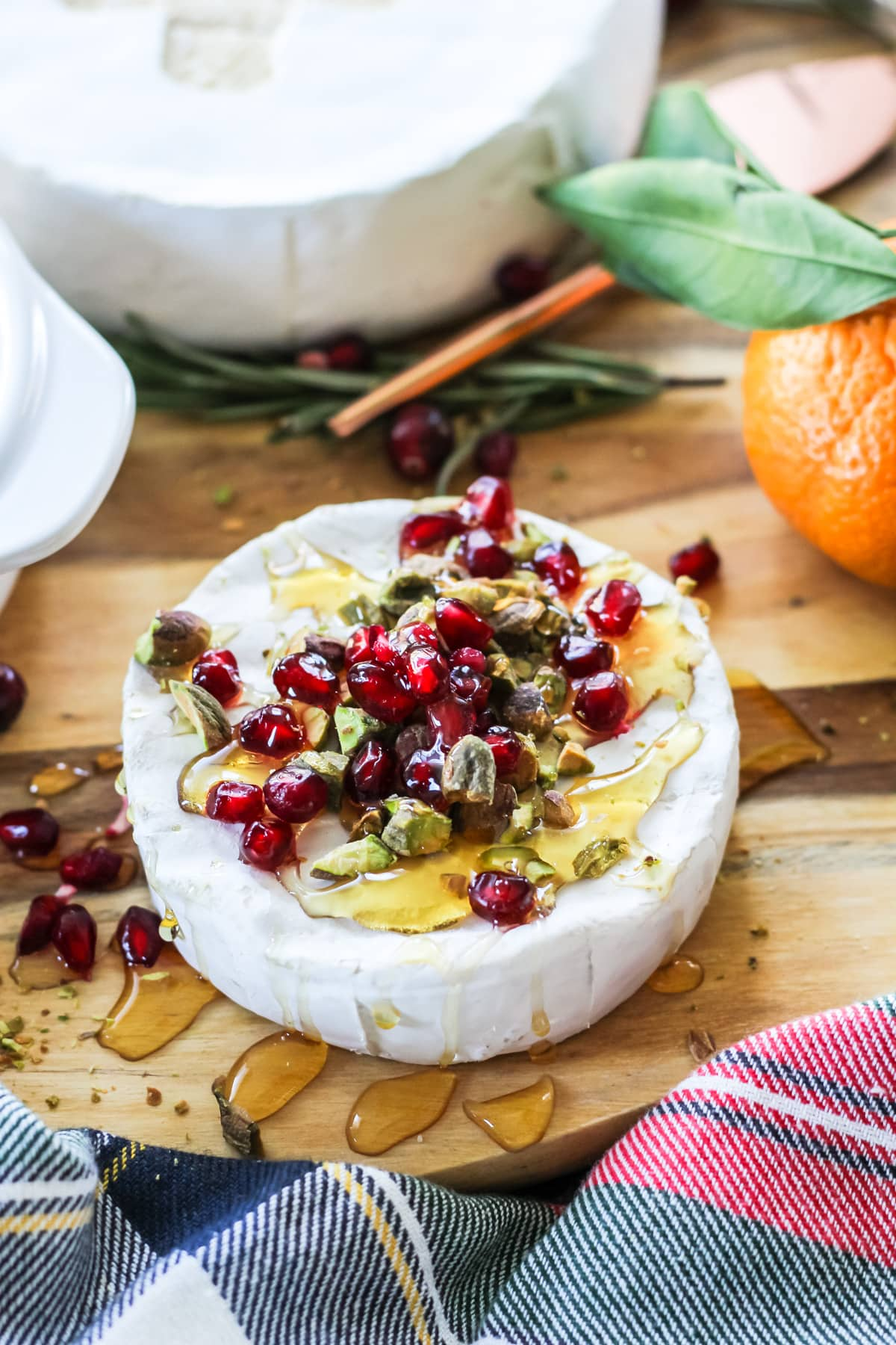 A wheel of Brie drizzled with honey, then topped with Pomegranate Seeds and Pistachios