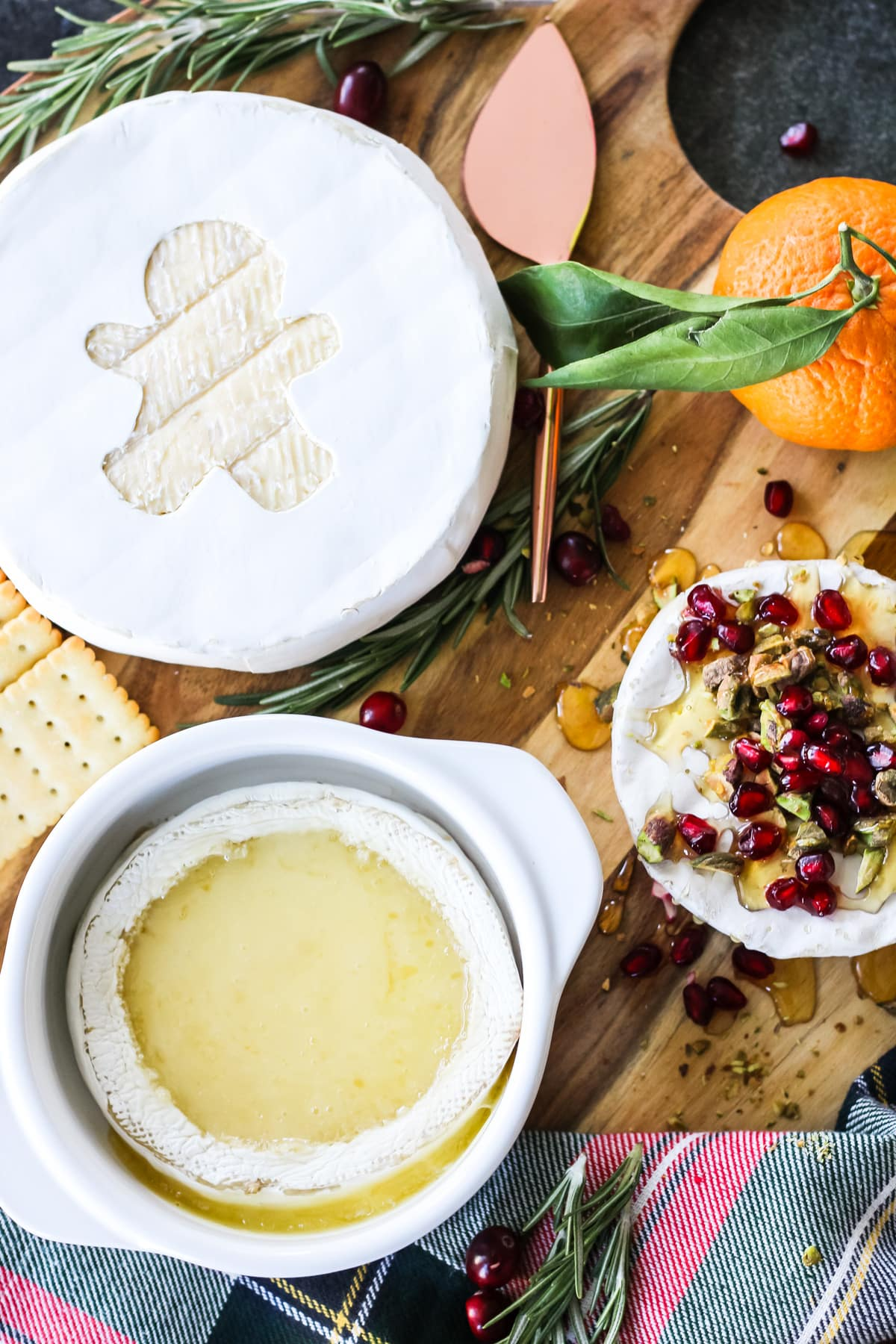 A cheese board with a baked Brie fondue, a wheel of Brie cheese with a gingerbread cut out and a small brie covered with honey, pomegranate seeds and pistachios
