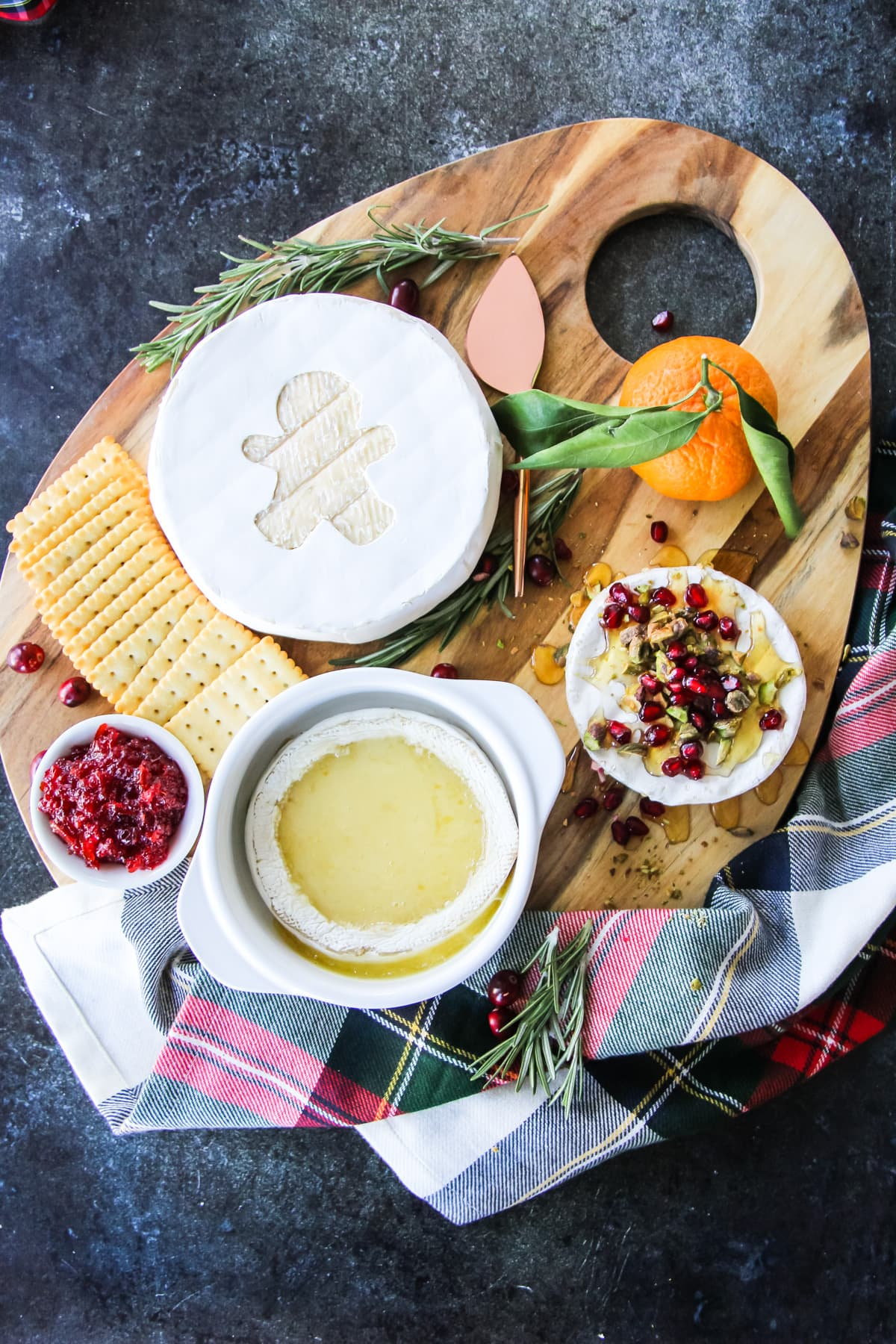 a wooden board with Christmas Appetizers like Brie, crackers and marmalade