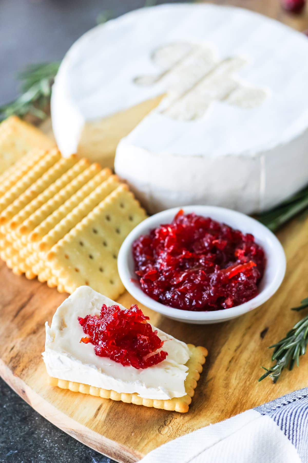 a cheese board with a wedge of Brie topped in cranberry orange marmalade