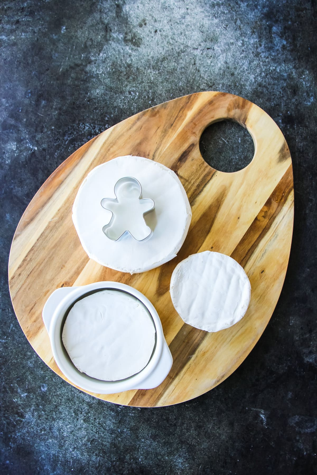 A cheese board with three wheels of Brie cheese