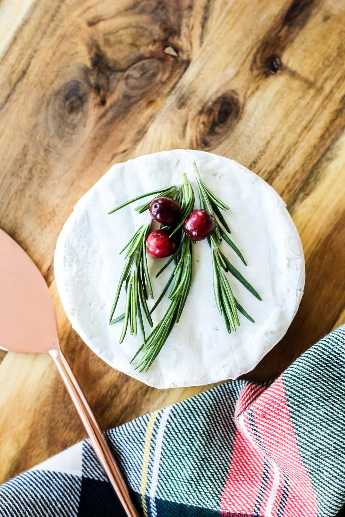 A small wheel of Brie topped with fresh rosemary and cranberries