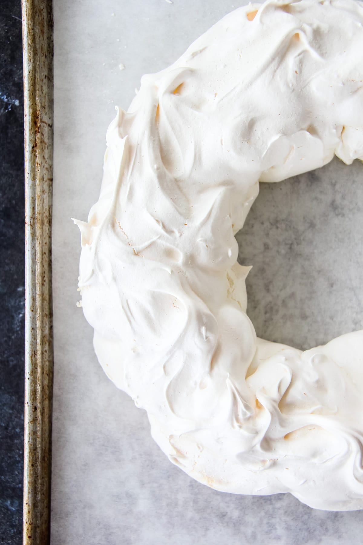 A top down view of a baking sheet with a baked pavlova in the shape of a wreath.
