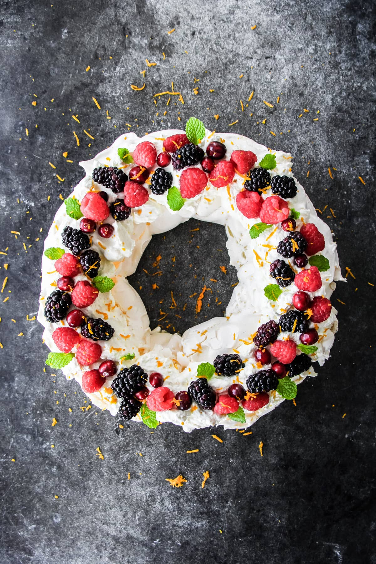 A top down view of a pavlova in the shape of a circle (wreath), decorated with fresh raspberries, blackberries, cranberries, mint leaves and orange zest!