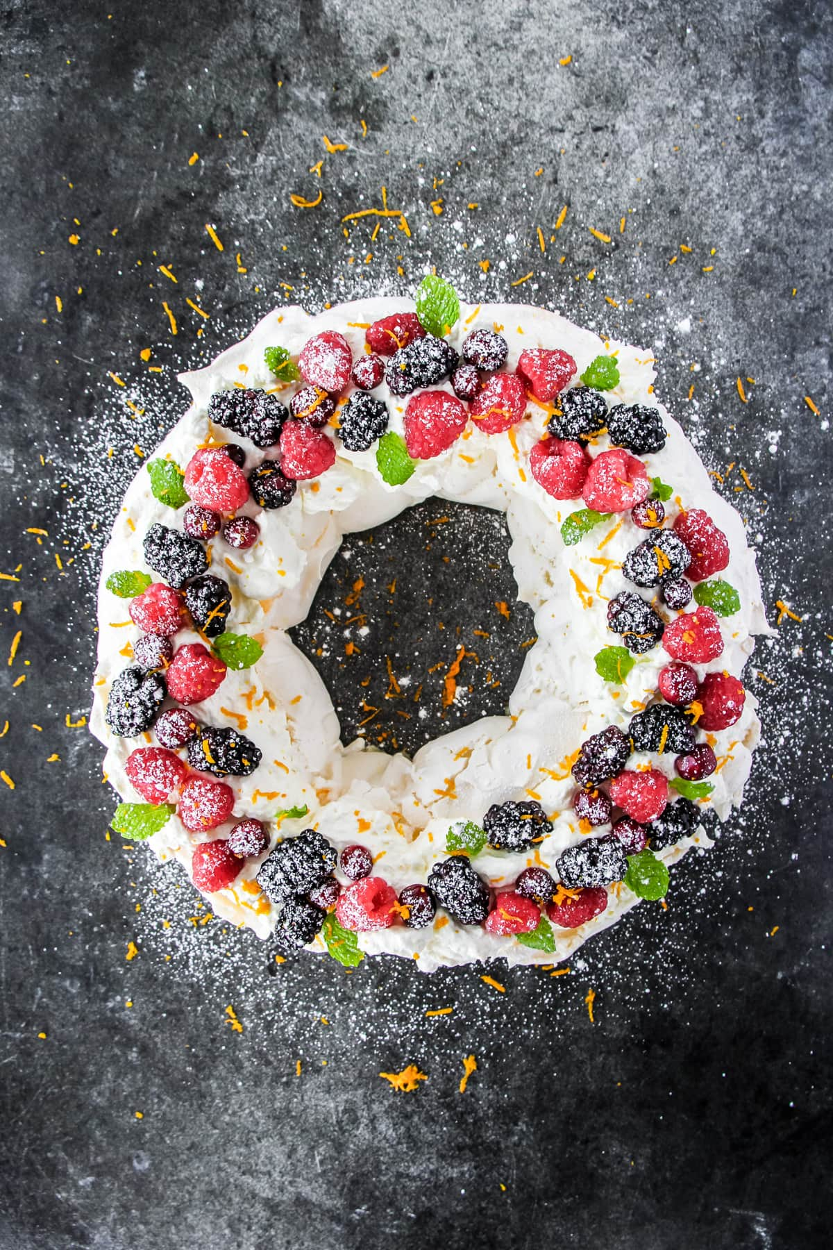 A top down view of a pavlova in the shape of a circle (wreath), decorated with fresh raspberries, blackberries, cranberries, mint leaves, orange zest and a dusting of confectioner's sugar