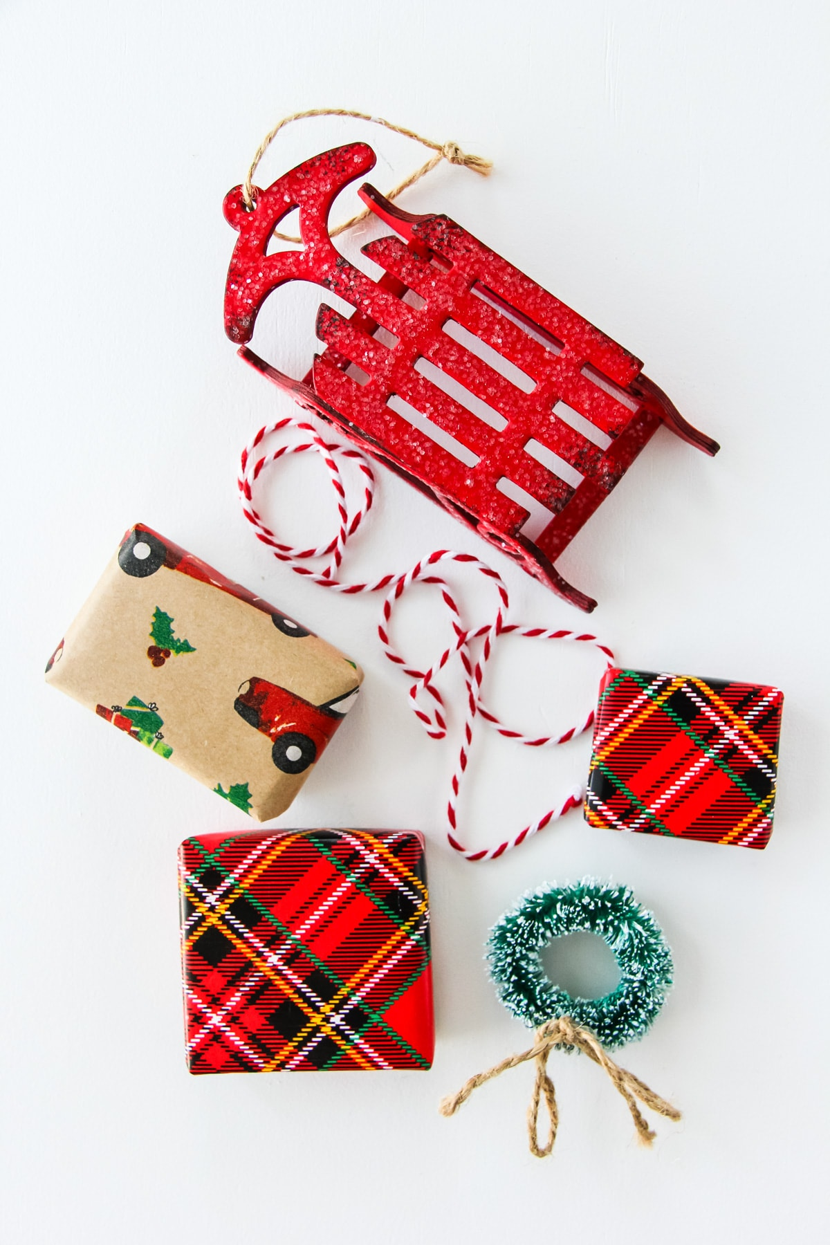 an image of a mini red sleigh, three wrapped gifts, a mini green wreath, a piece of red and white string
