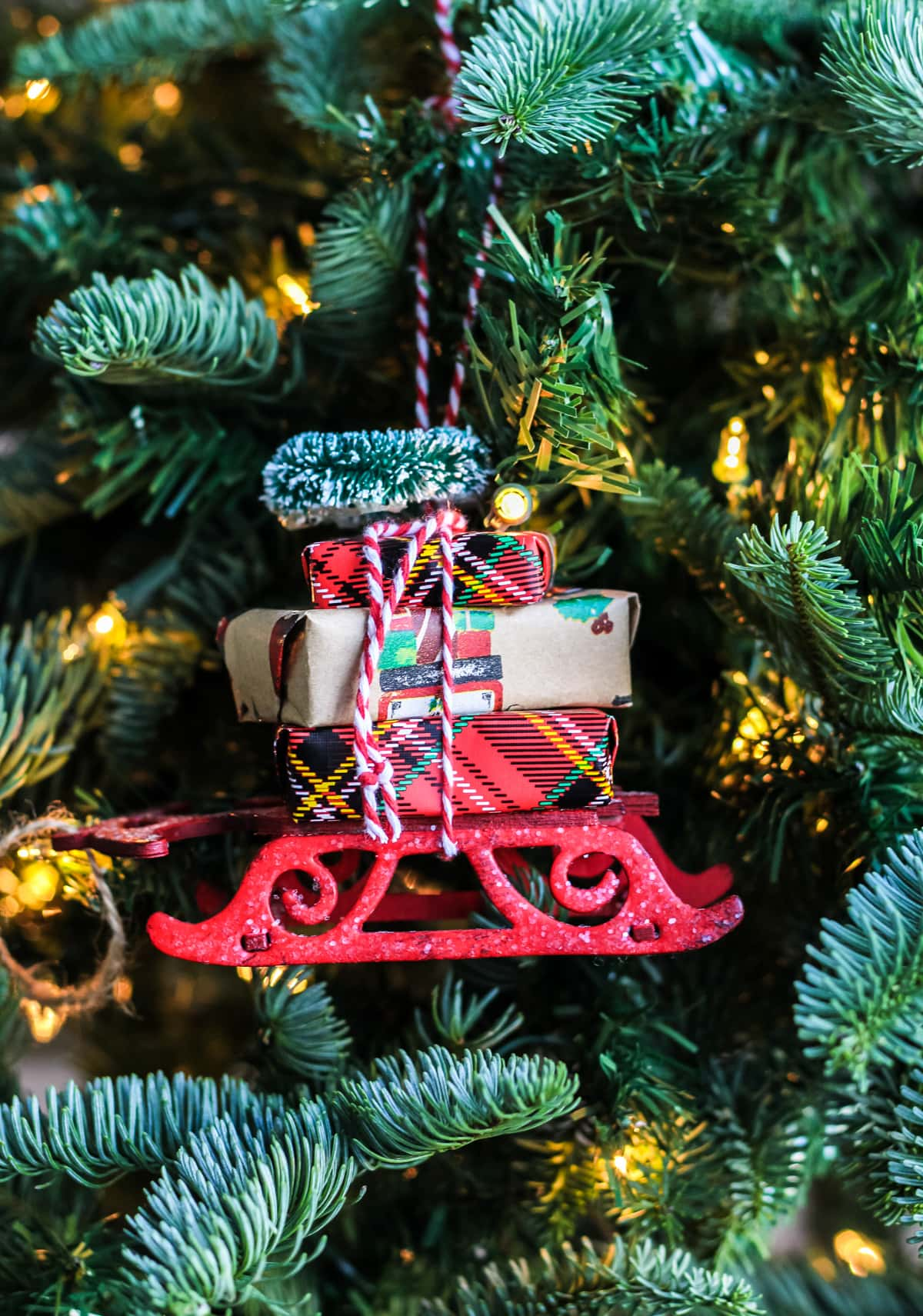 A Christmas Sleigh Ornament hanging on a tree
