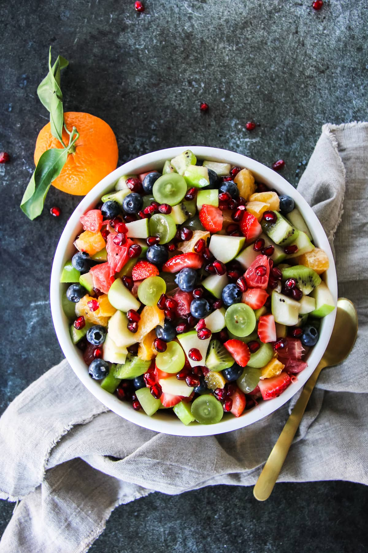 a bowl of fruit salad on a linen napkin with a spoon