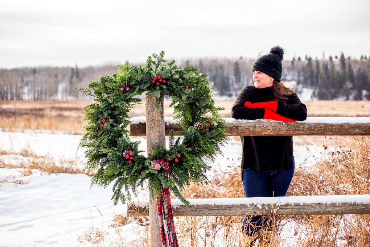 a lady leaning on a fence next to a evergreen wreath