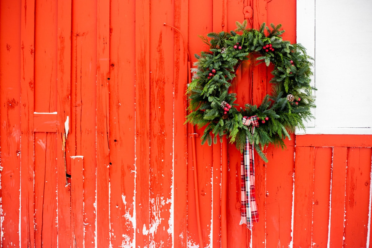 an evergreen wreath hanging on a red barn wall