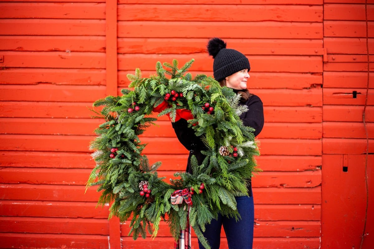 a lady holding an evergreen wreath against a red barn wall