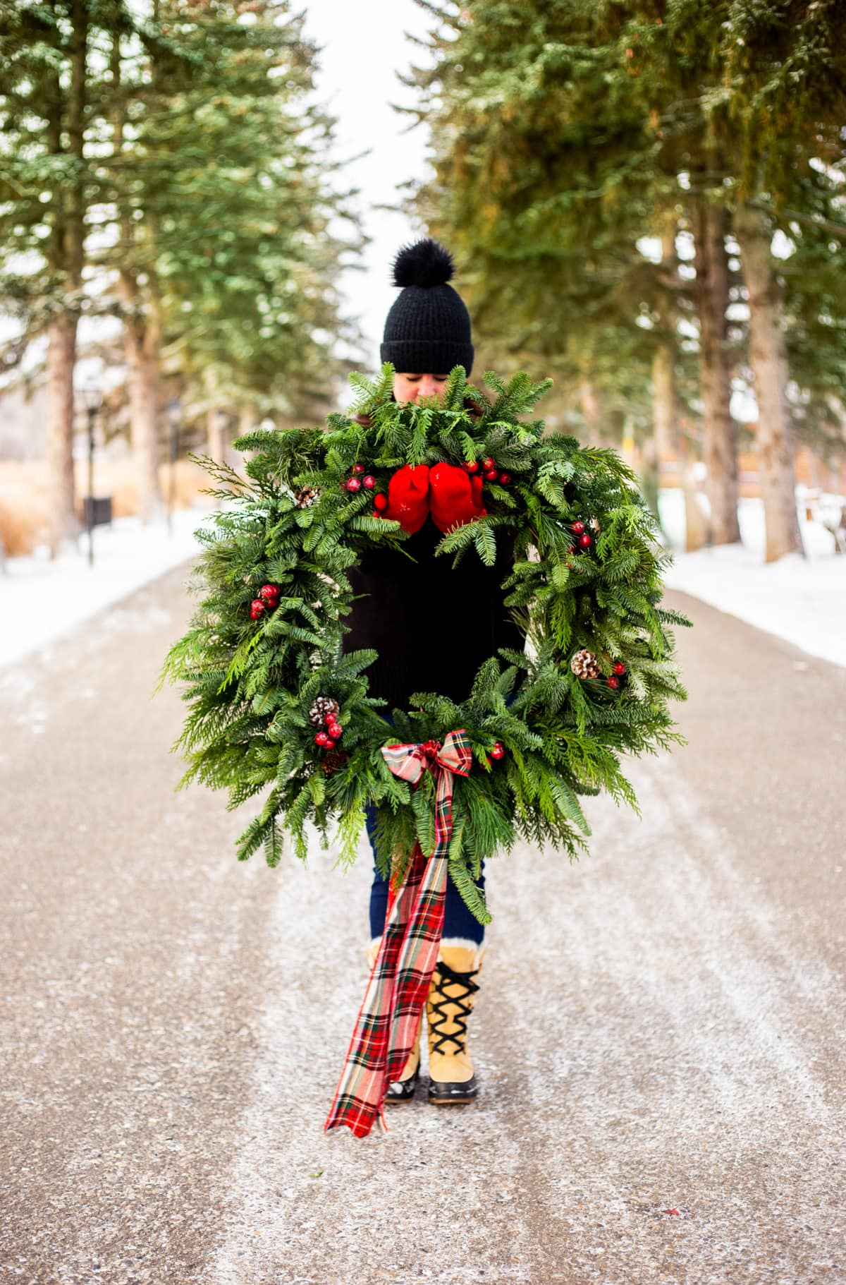 a lady holding out a wreath in front of her
