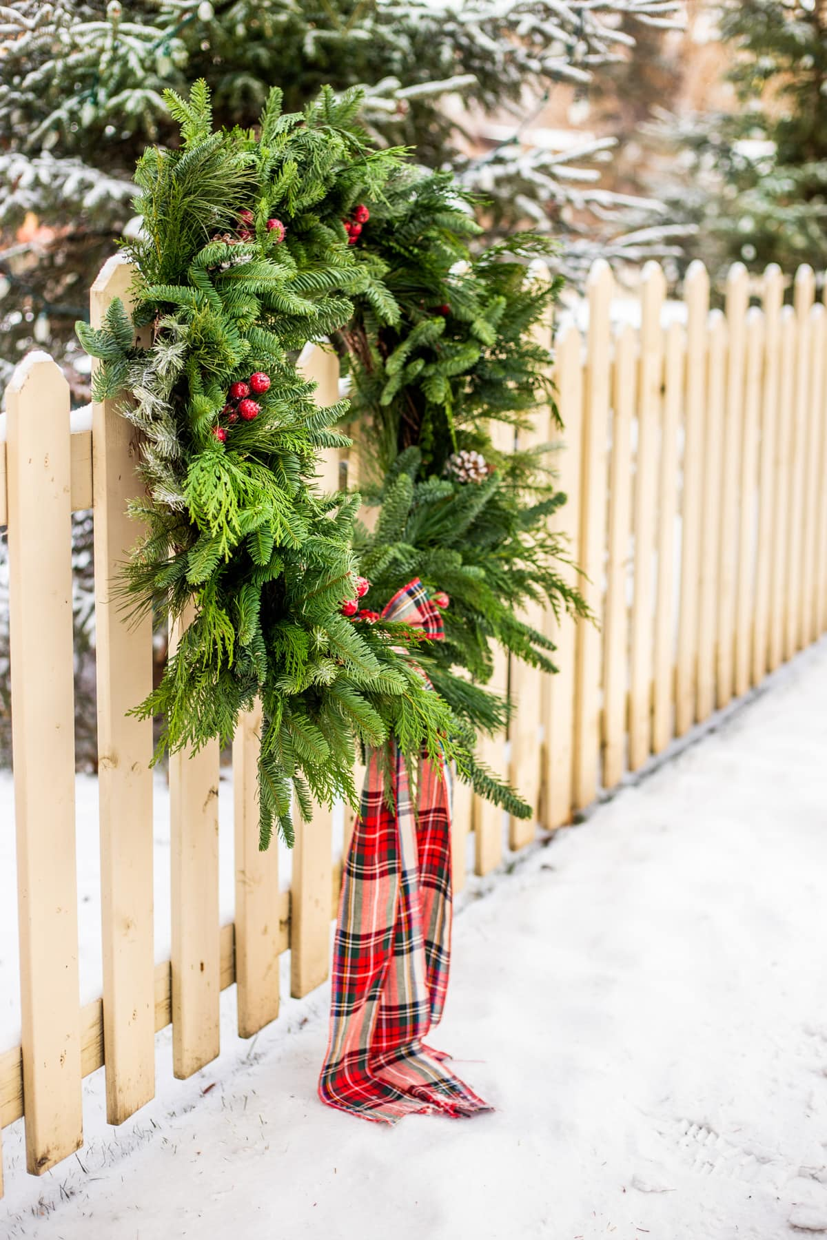 an evergreen wreath hanging on a fence