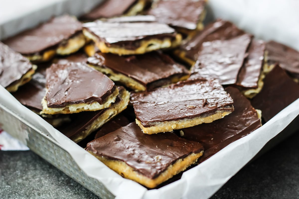 a tin dish lined with parchment paper is filled with squares of Christmas Crack