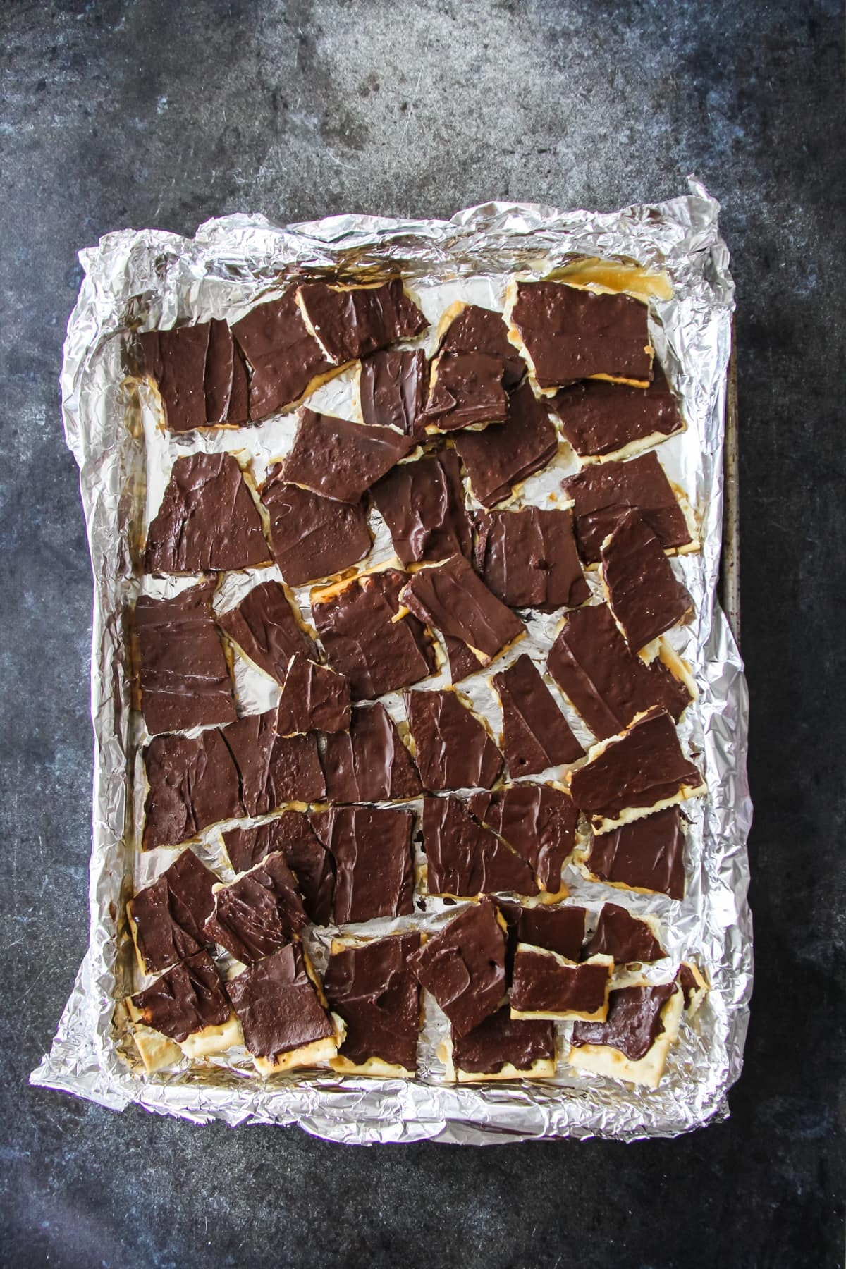 a tin foil lined baking sheet with squares of chocolate and caramel covered crackers