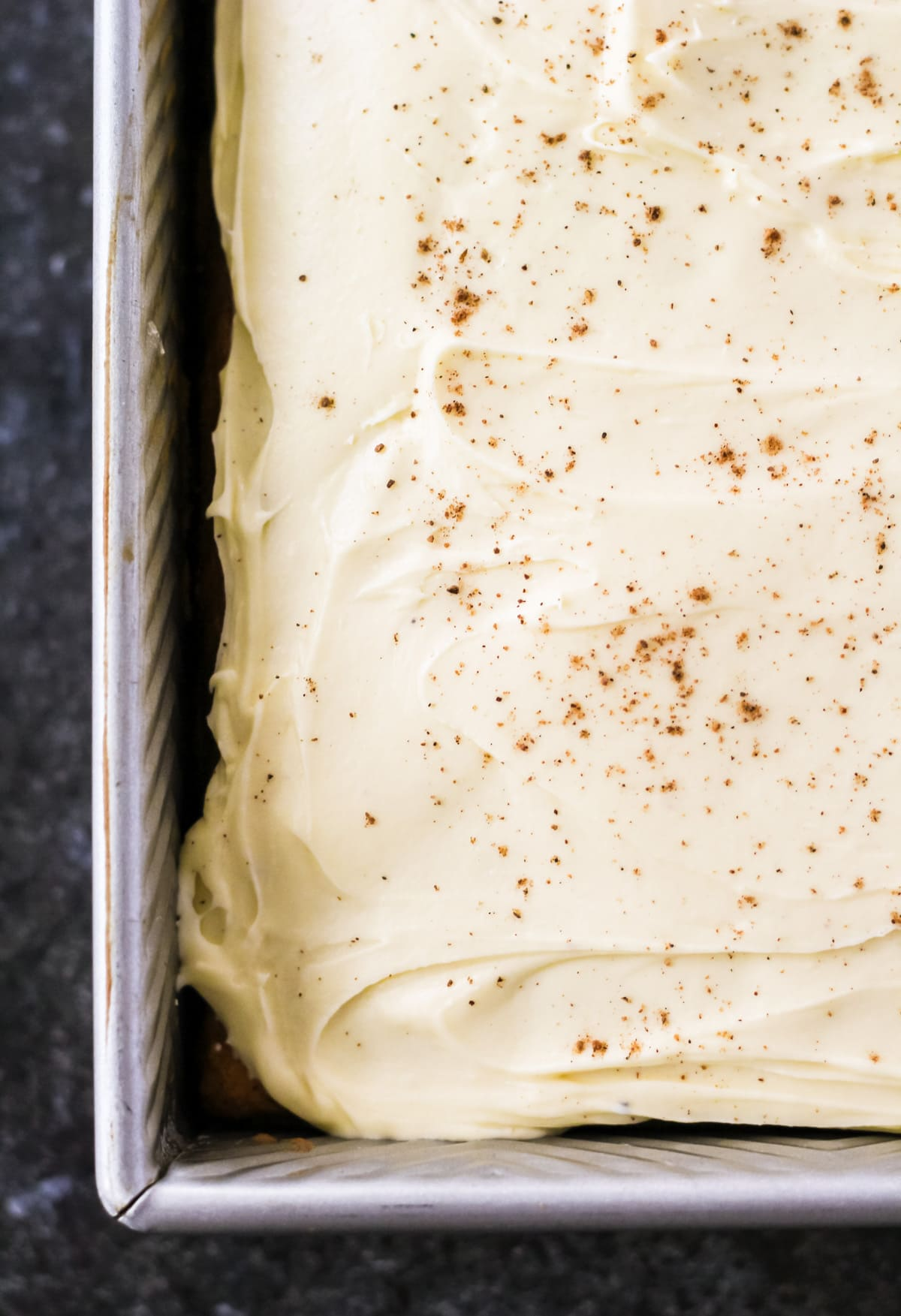 a top down view of the corner of a frosted eggnog cake in a cake pan. sprinkled wth nutmeg.