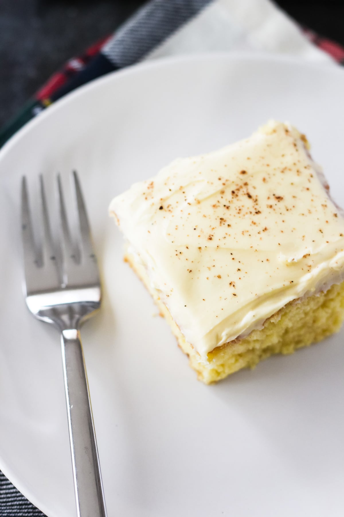 a square of frosted eggnog cake on a plate with a fork