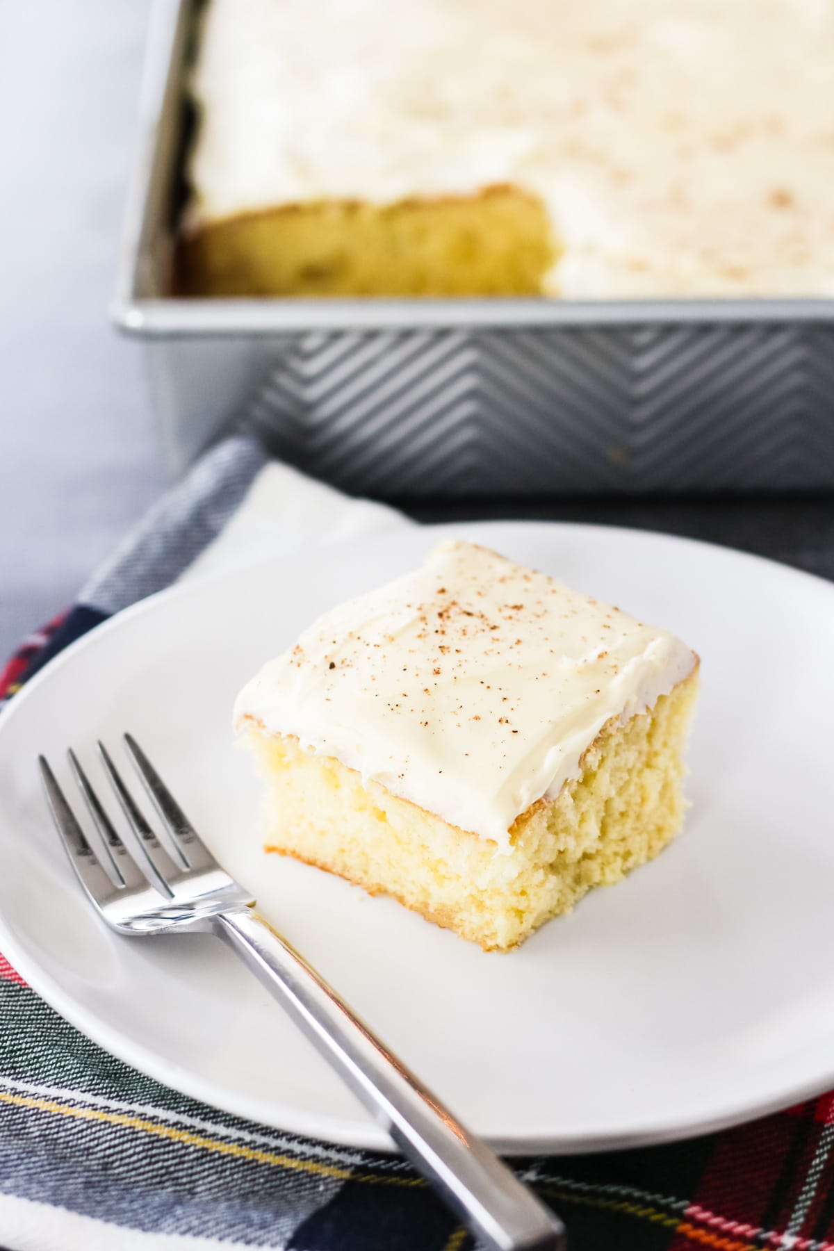 a square of frosted eggnog cake on a plate with a fork. in the background is the pan of eggnog cake with a piece cut out of it