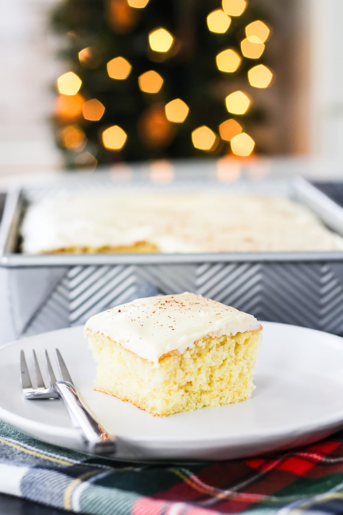 a square of frosted eggnog cake on a plate with a fork. in the background is the pan of eggnog cake with a piece cut out of it. in the far background is Bokeh