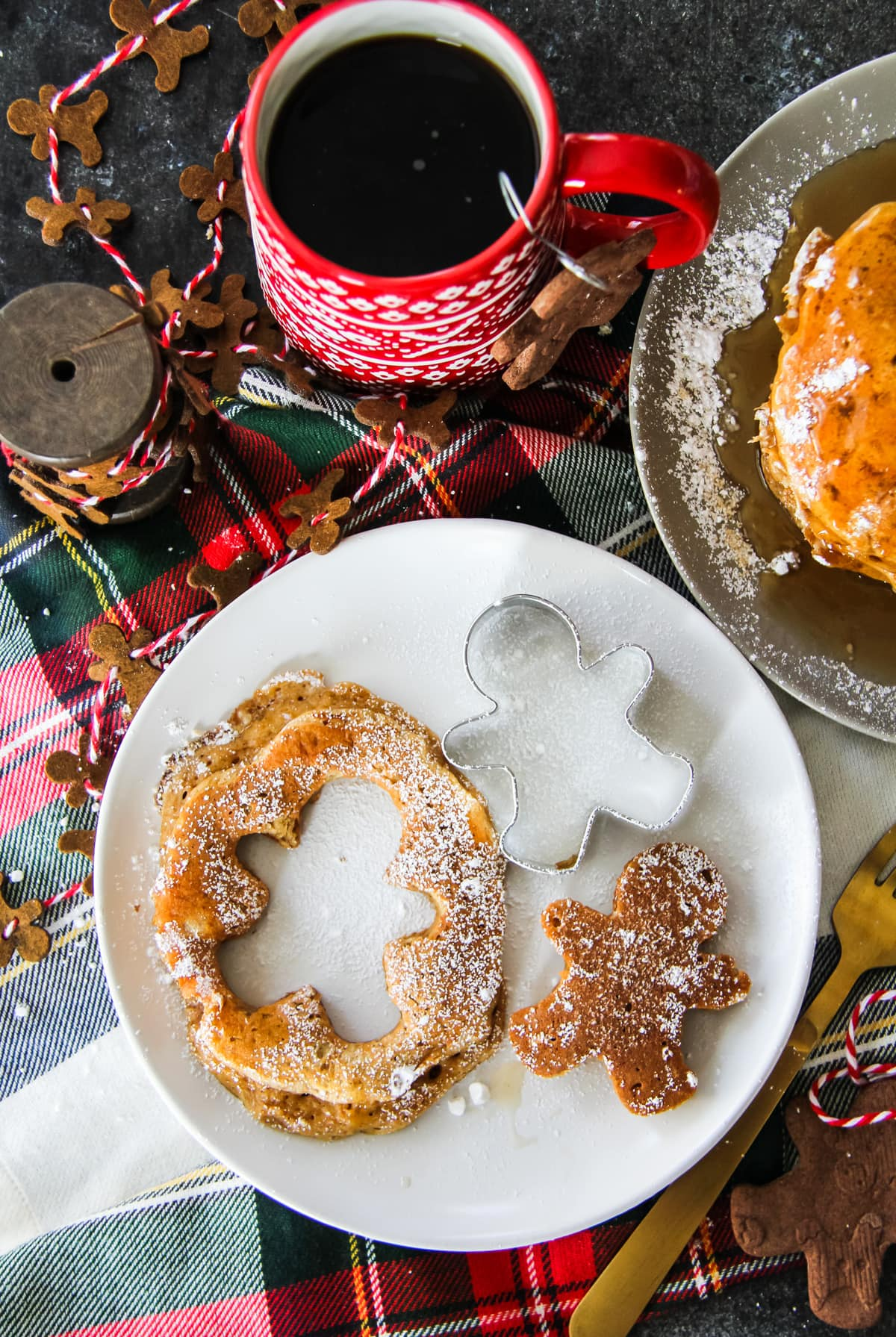a Gingerbread Pancake on a plate with a gingerbread man cut out of the centre. background includes a stack of pancakes, a cup of coffee, a plaid napkin and a felt mini gingerbread man garland