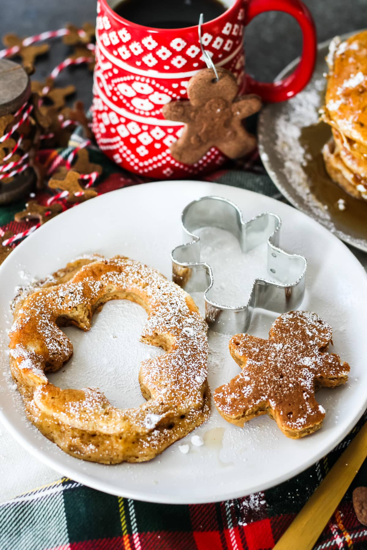 a Gingerbread Pancake on a plate with a gingerbread man cut out of the centre. background includes a cup of coffee and a felt mini gingerbread man garland