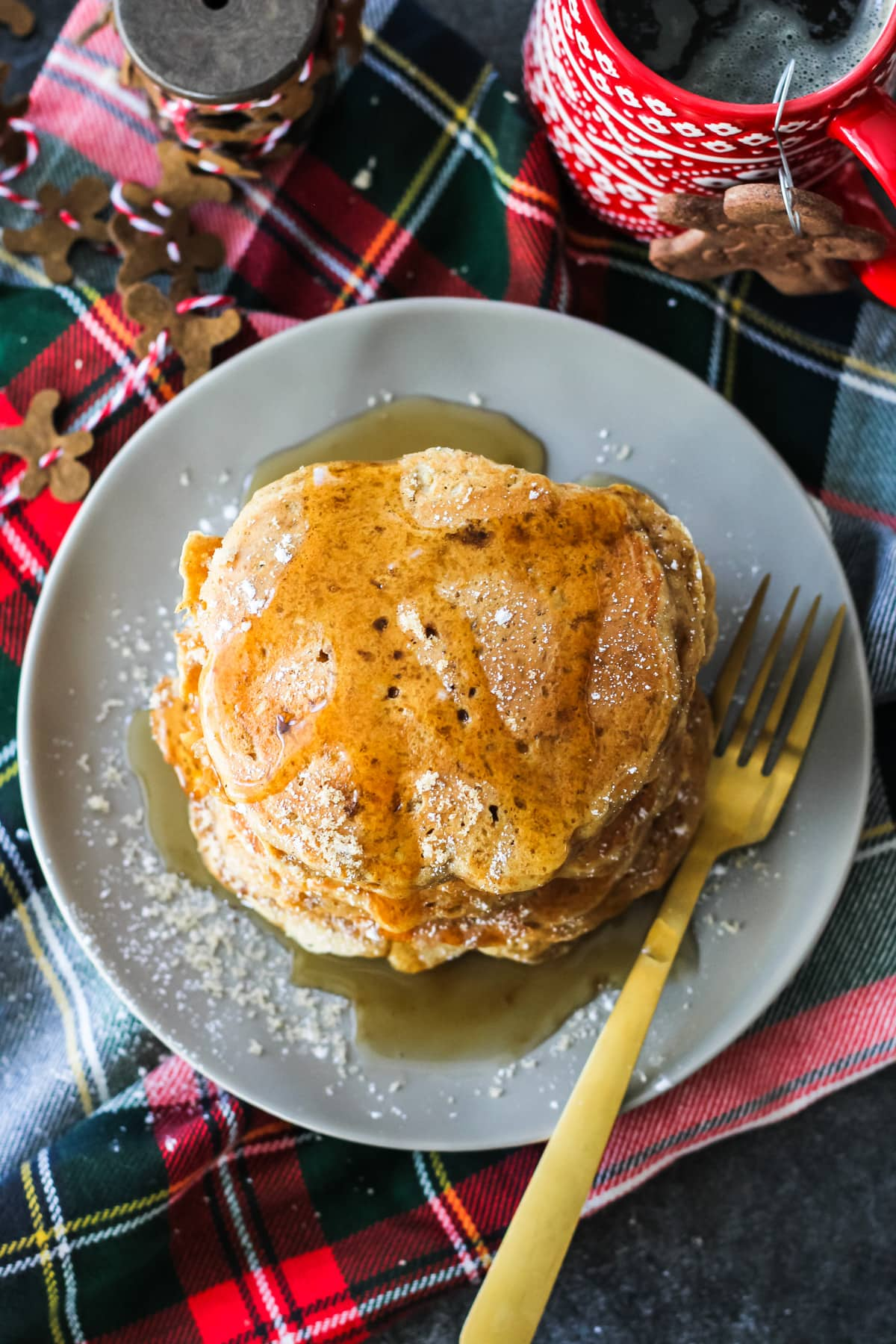 a top down view of Gingerbread Pancakes drizzled with syrup. sitting on a background of plaid napkins