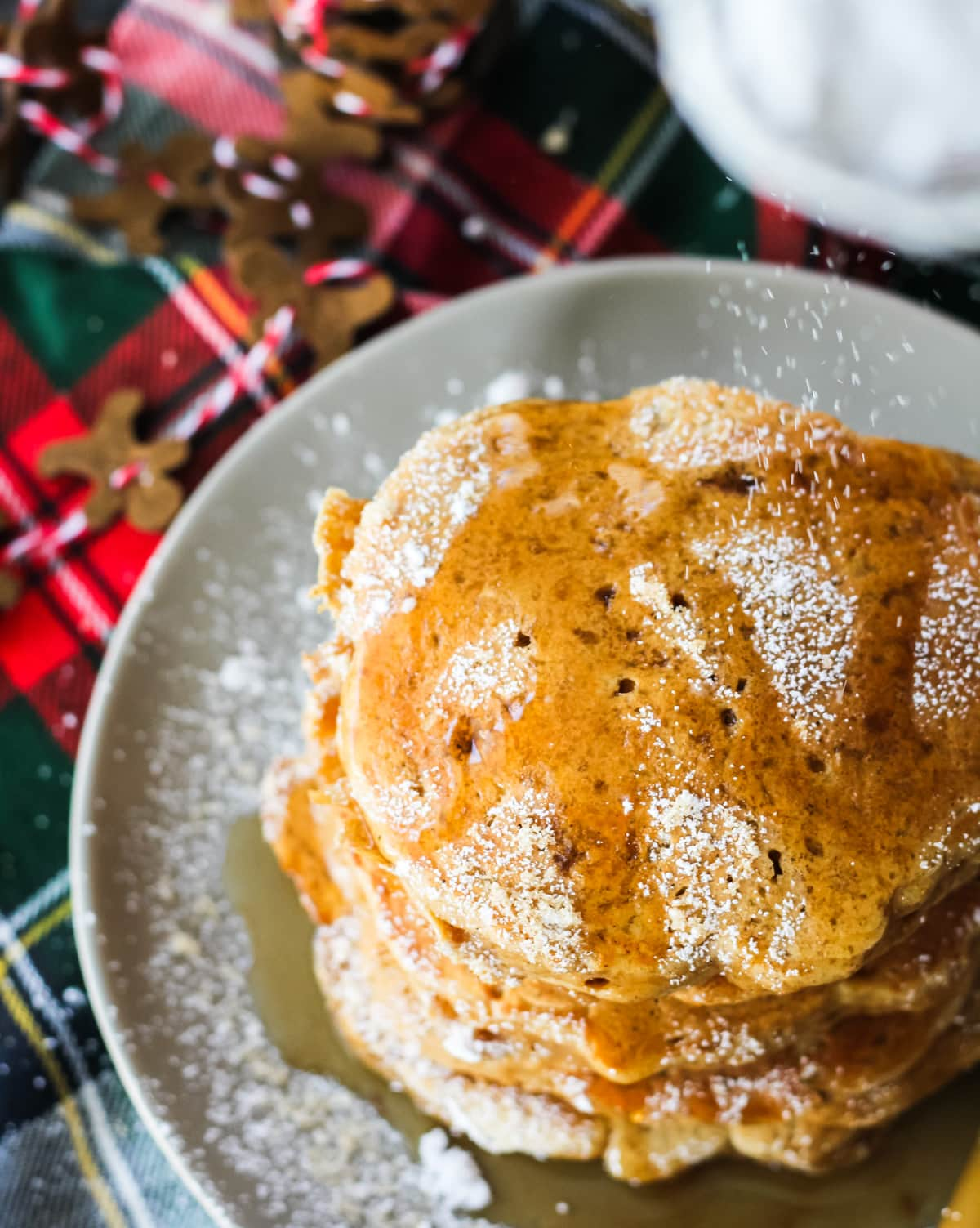 a top down view of Gingerbread Pancakes being sprinkled with icing sugar