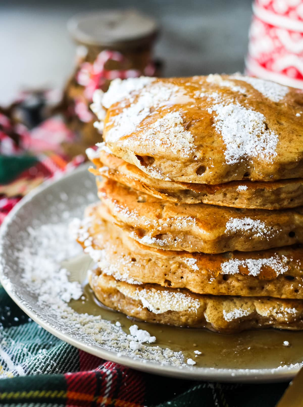 a side view of a stack of Gingerbread Pancakes sprinkled with icing sugar