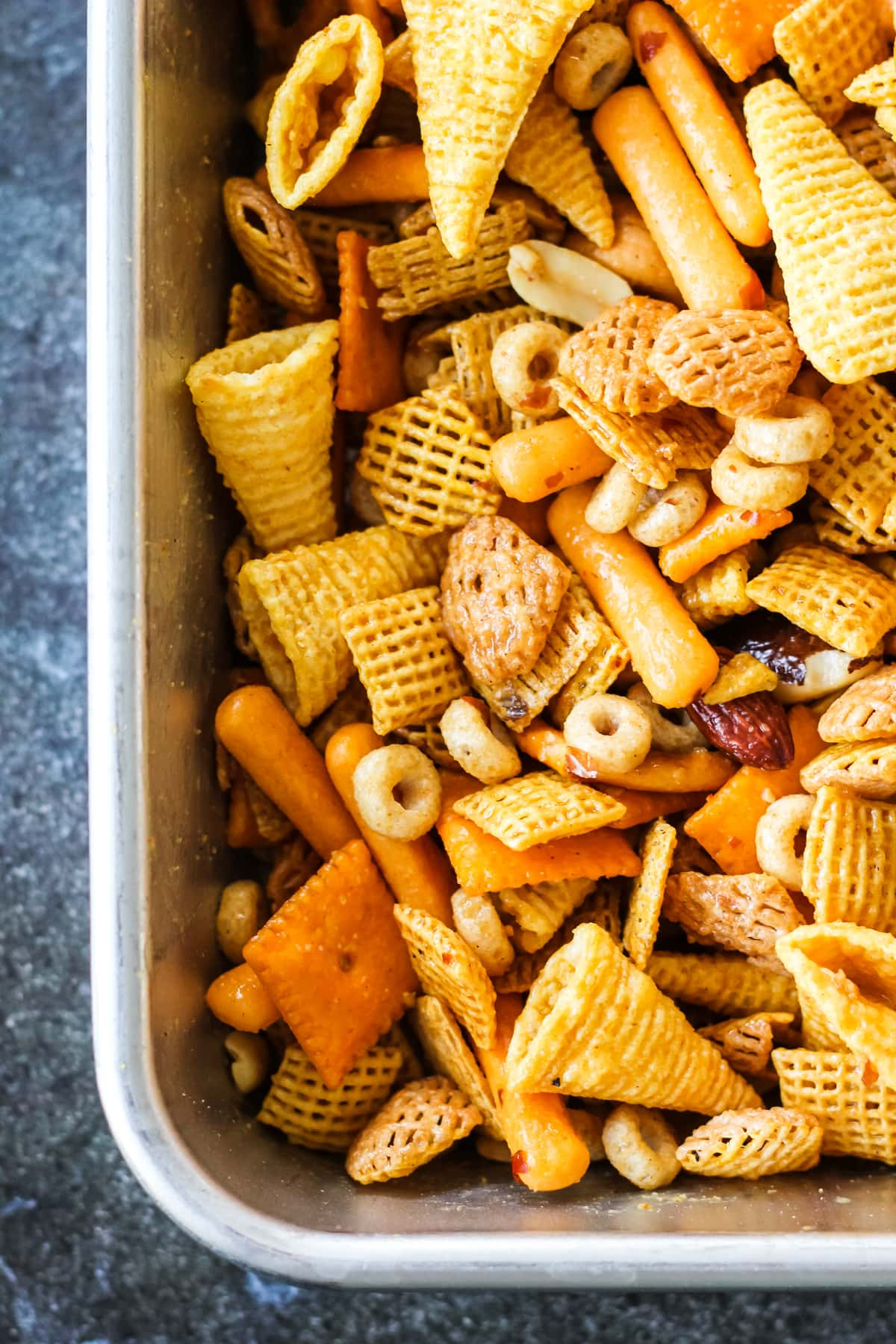a close up of a tray of Nuts and Bolts with cheerios, bugles, pretzels, nuts and cereal