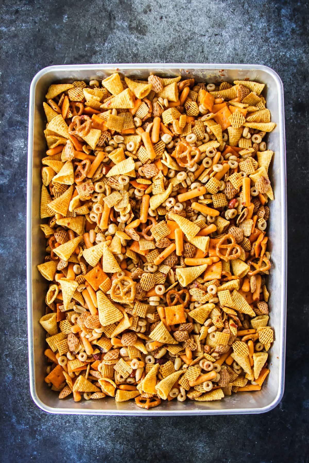 a baking tray of Nuts and Bolts with cheerios, bugles, pretzels, nuts and cereal