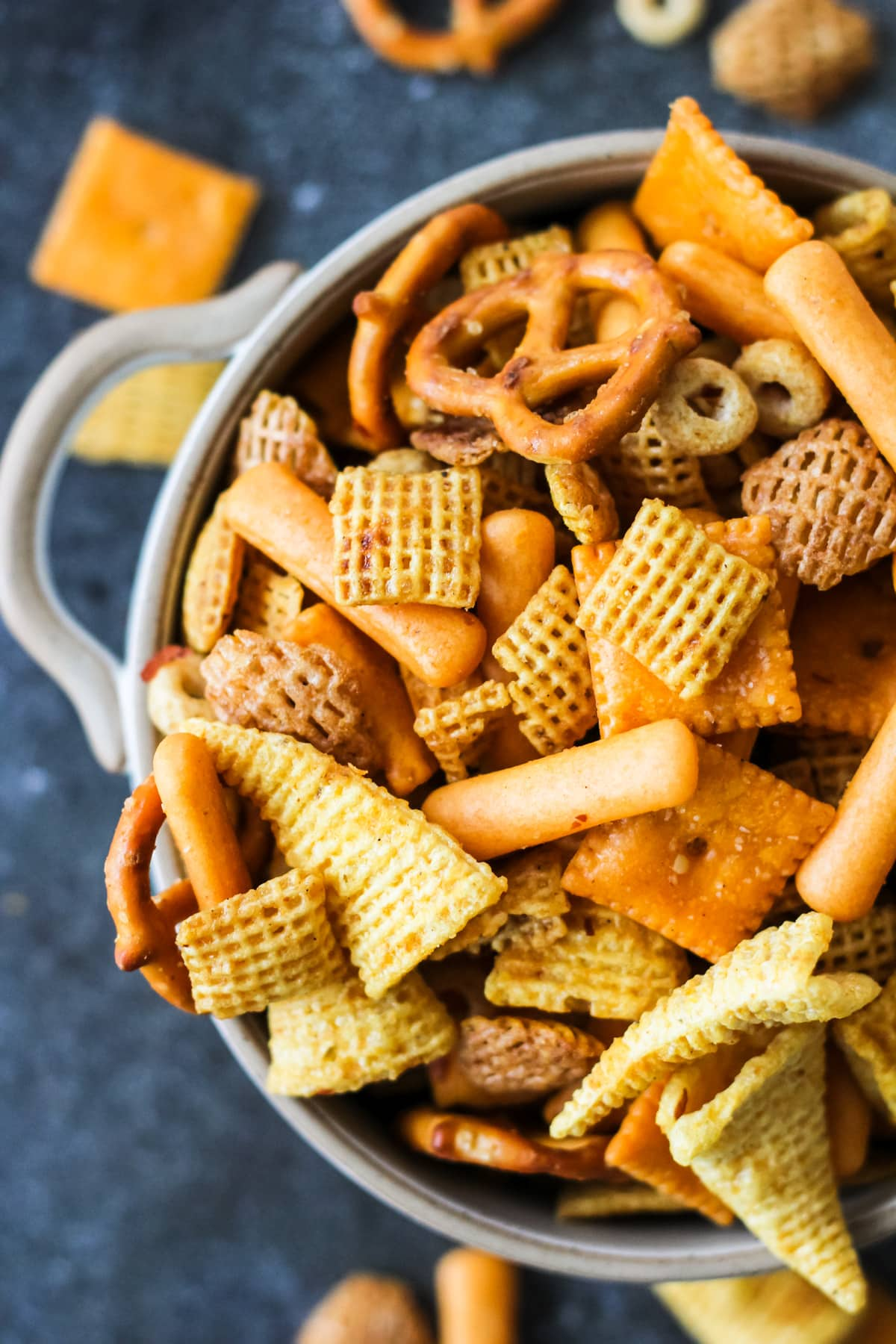 a top down close up of a bowl of Nuts and Bolts with cheerios, bugles, pretzels, nuts and cereal