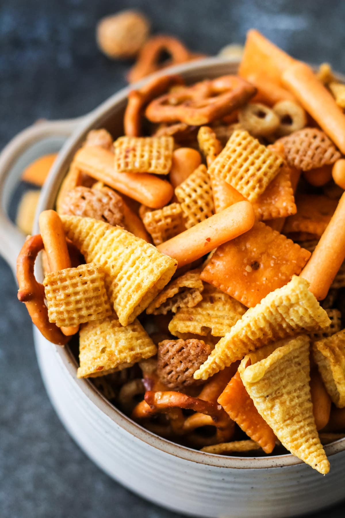 a close up of a bowl of Nuts and Bolts with cheerios, bugles, pretzels, nuts and cereal