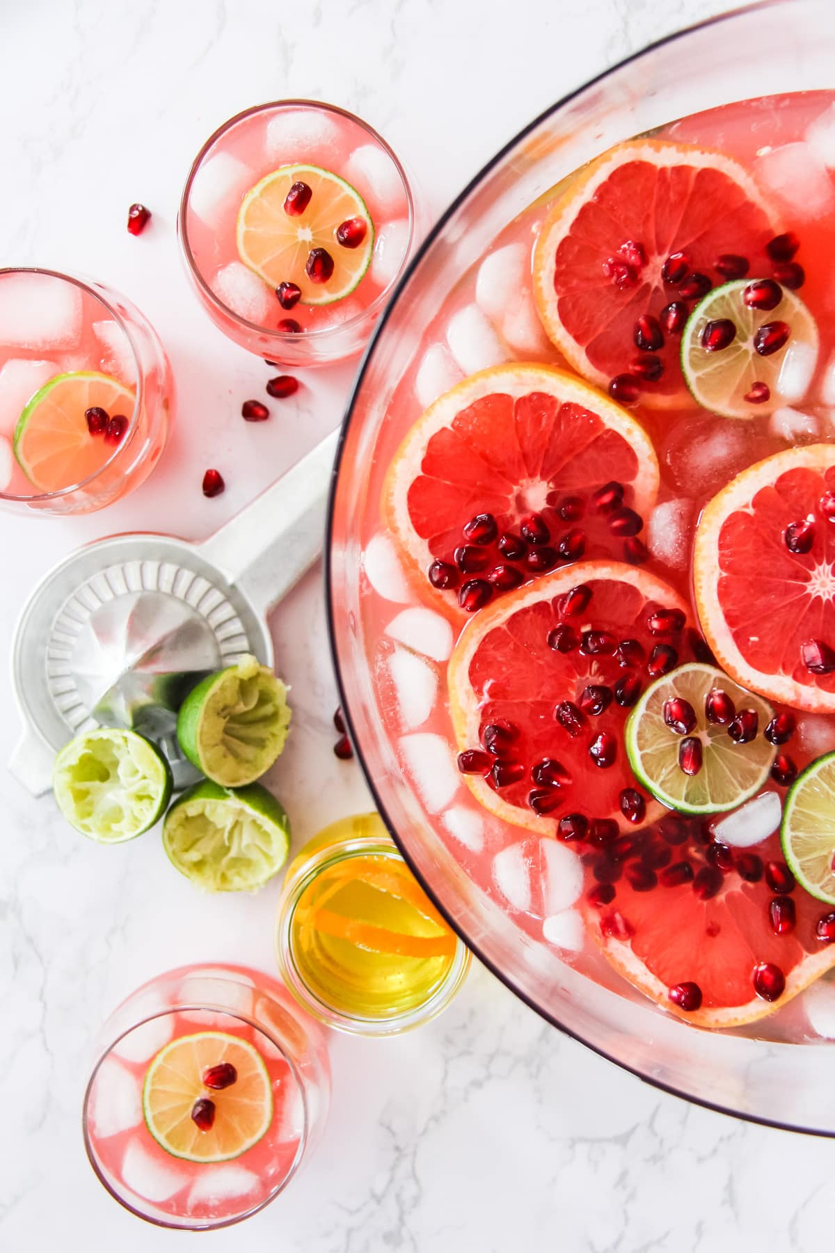 a top down view of half of a bowl of grapefruit punch. in the background are cups of punch, a juicer, juiced limes and a bottle of orange syrup