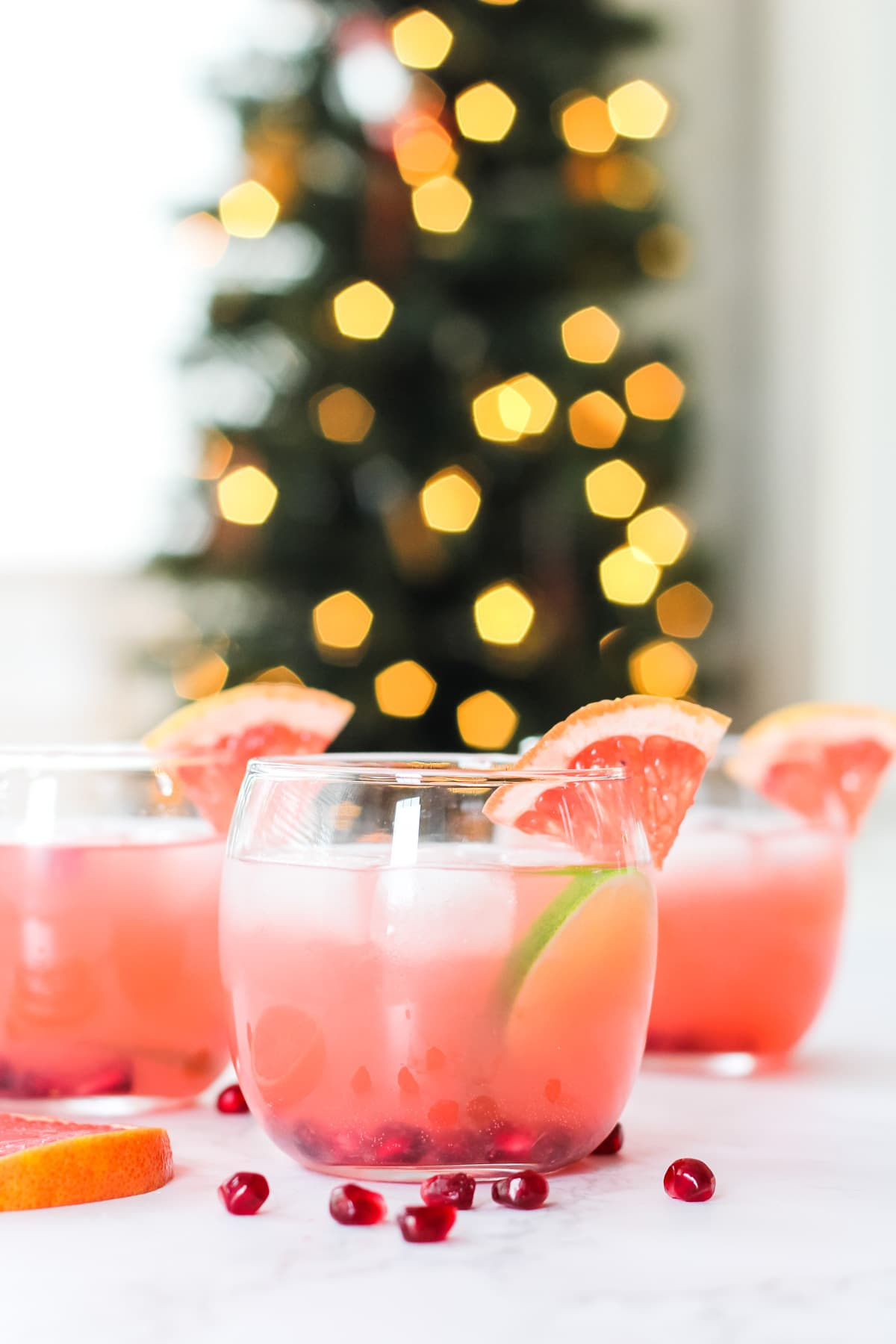 three cups of grapefruit punch set against a bokeh background