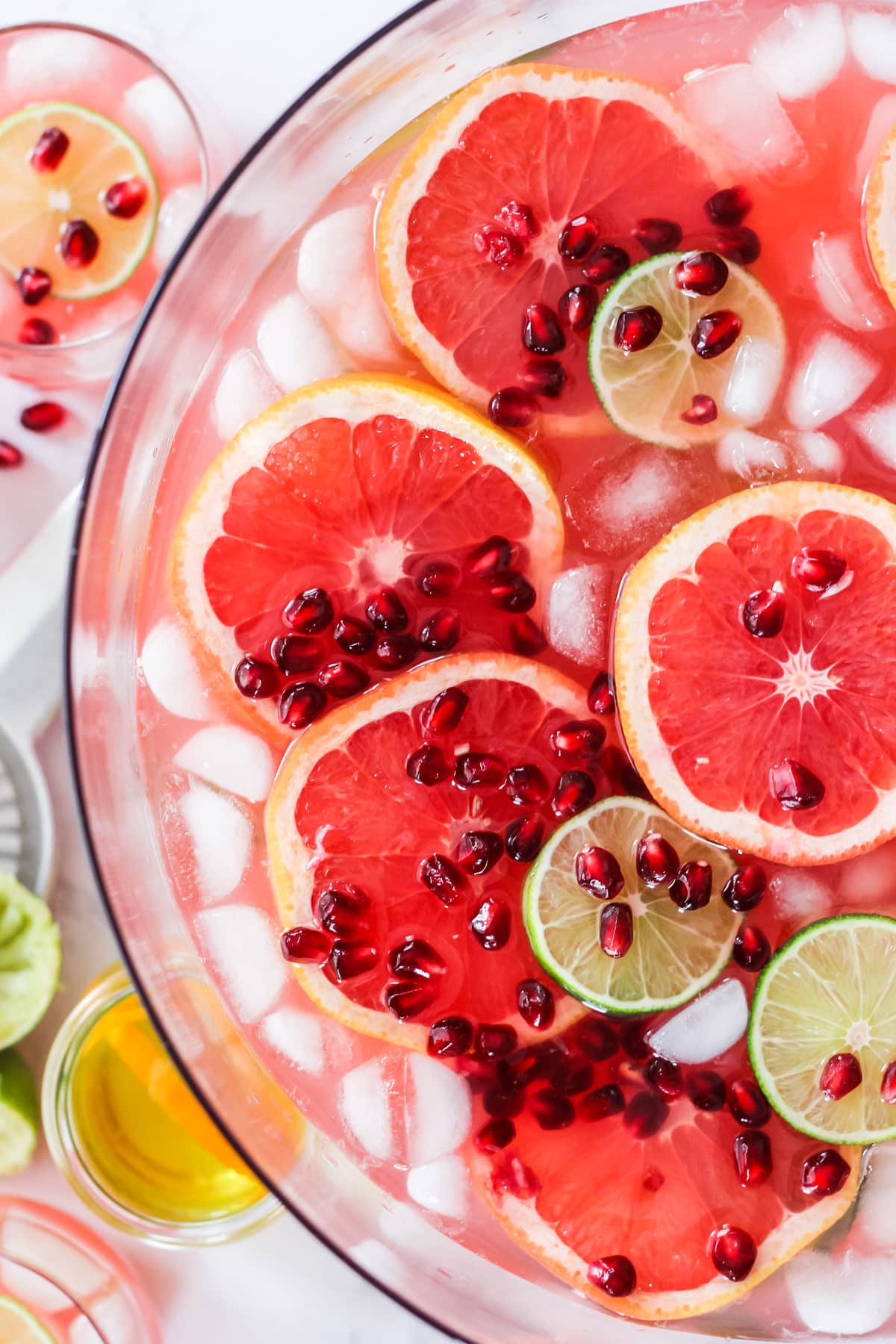 a top down half view of a bowl of grapefruit punch with slices of grapefruit, limes and pomegranate seeds