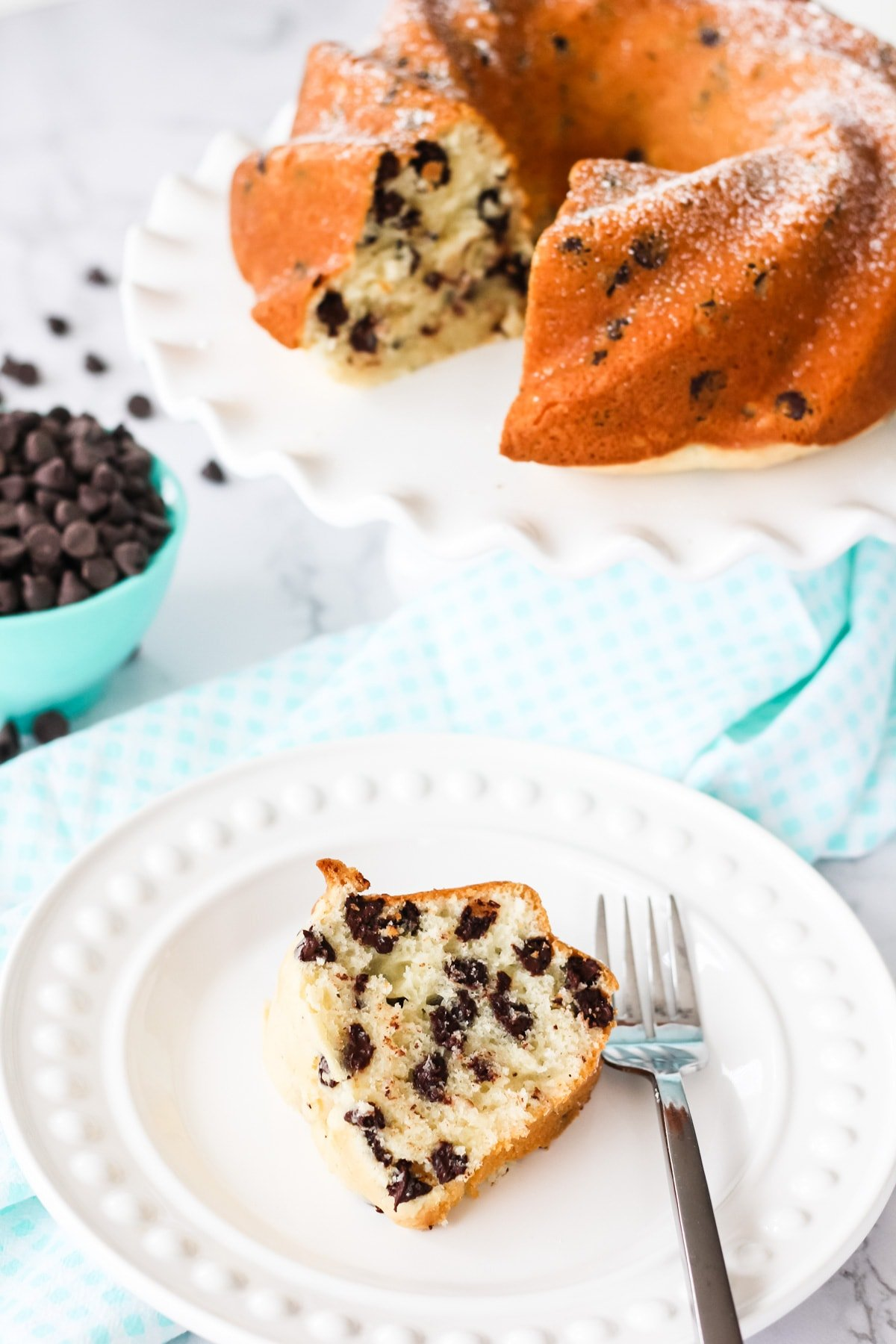 a slice of Chocolate Chip Bundt Cake on a white plate with a fork. in the background is the bundt cake and a bowl of chocolate chips and a teal gingham napkin
