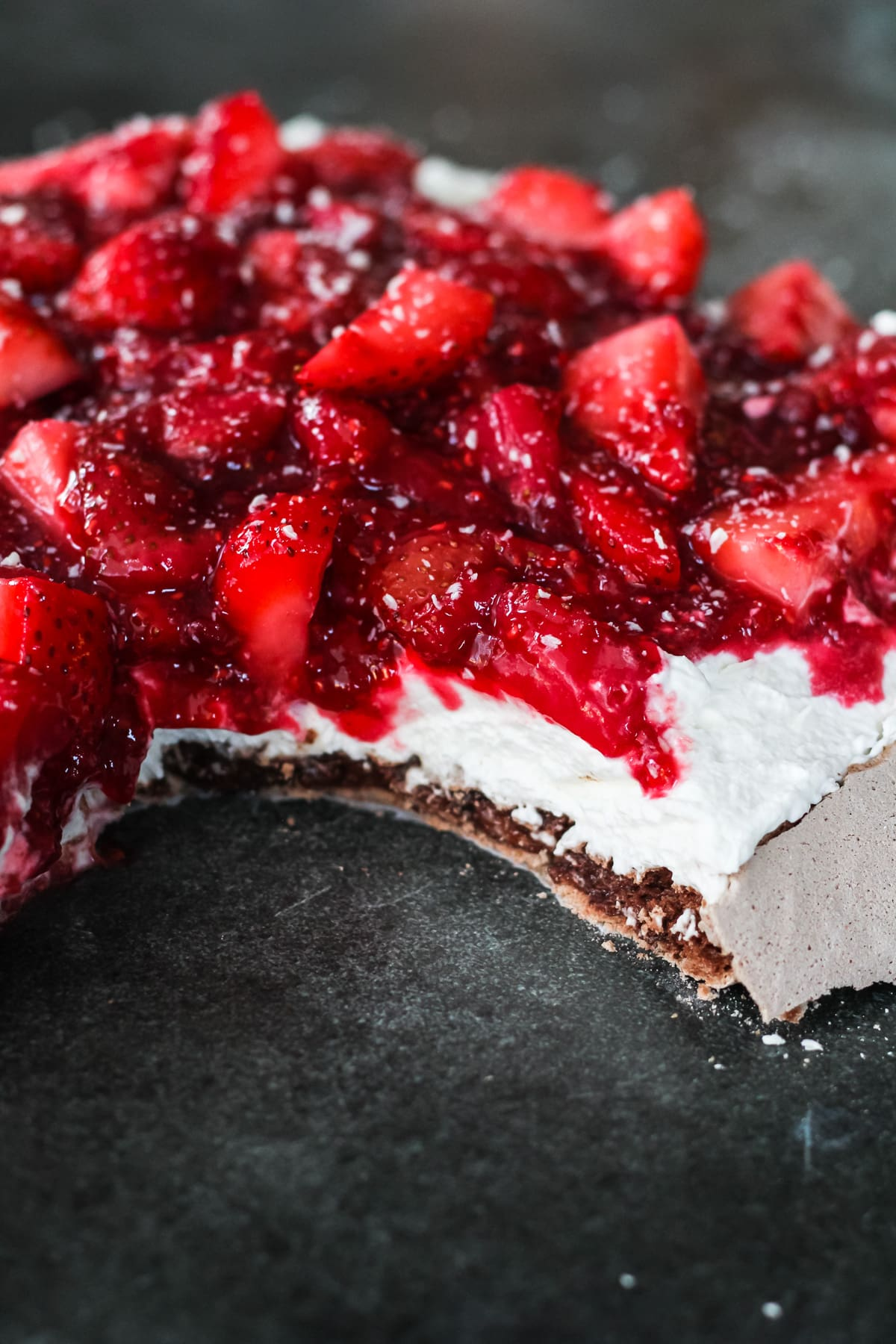 a side view of a chocolate pavlova showing the layers of chocolate meringue, whipping cream and strawberries