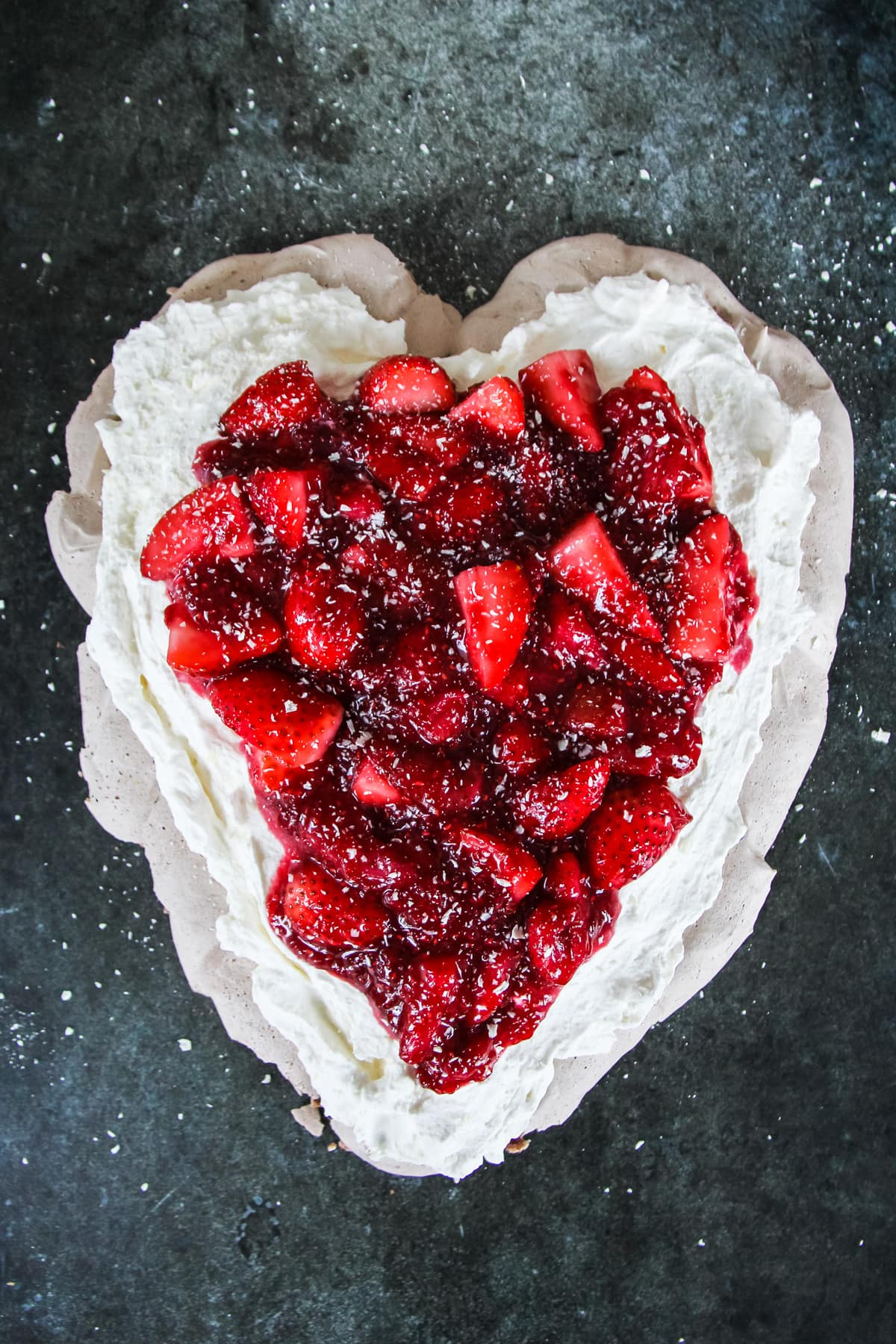 a heart shaped chocolate pavlova with layers of whipping cream and strawberries. on a dark background