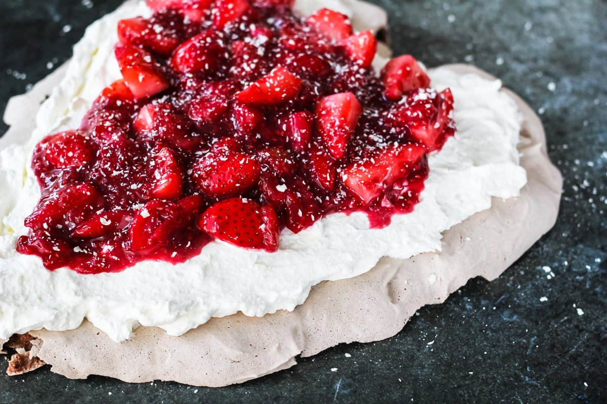 a side view of a chocolate pavlova showing the layers of whipping cream and strawberries