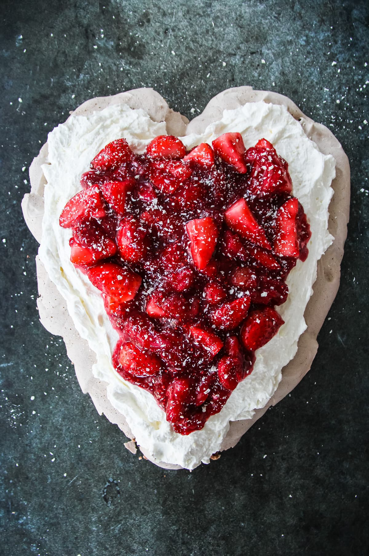 A top down view of a Valentine's Day Chocolate Pavlova topped with whipped cream and Strawberries