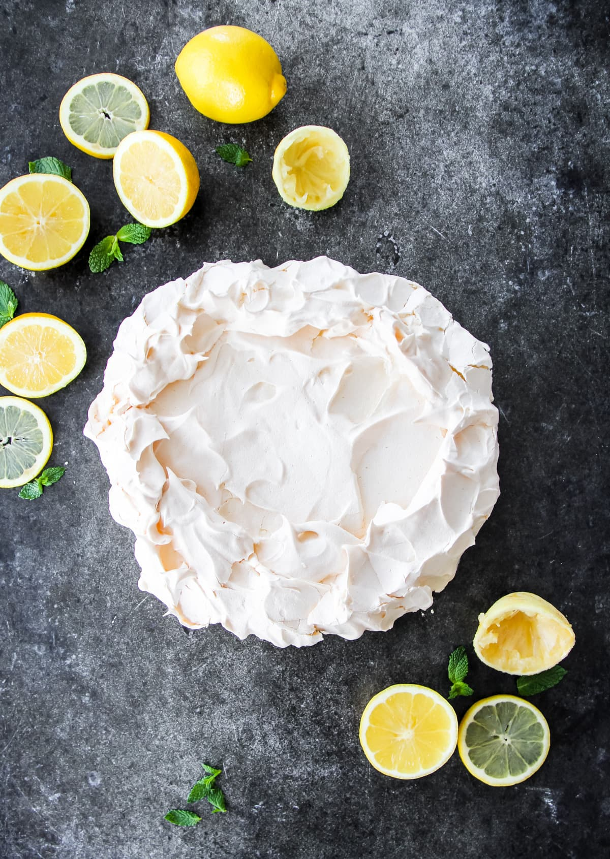 a top down view of a pavlova meringue. in the background are sliced lemons and sprigs of mint