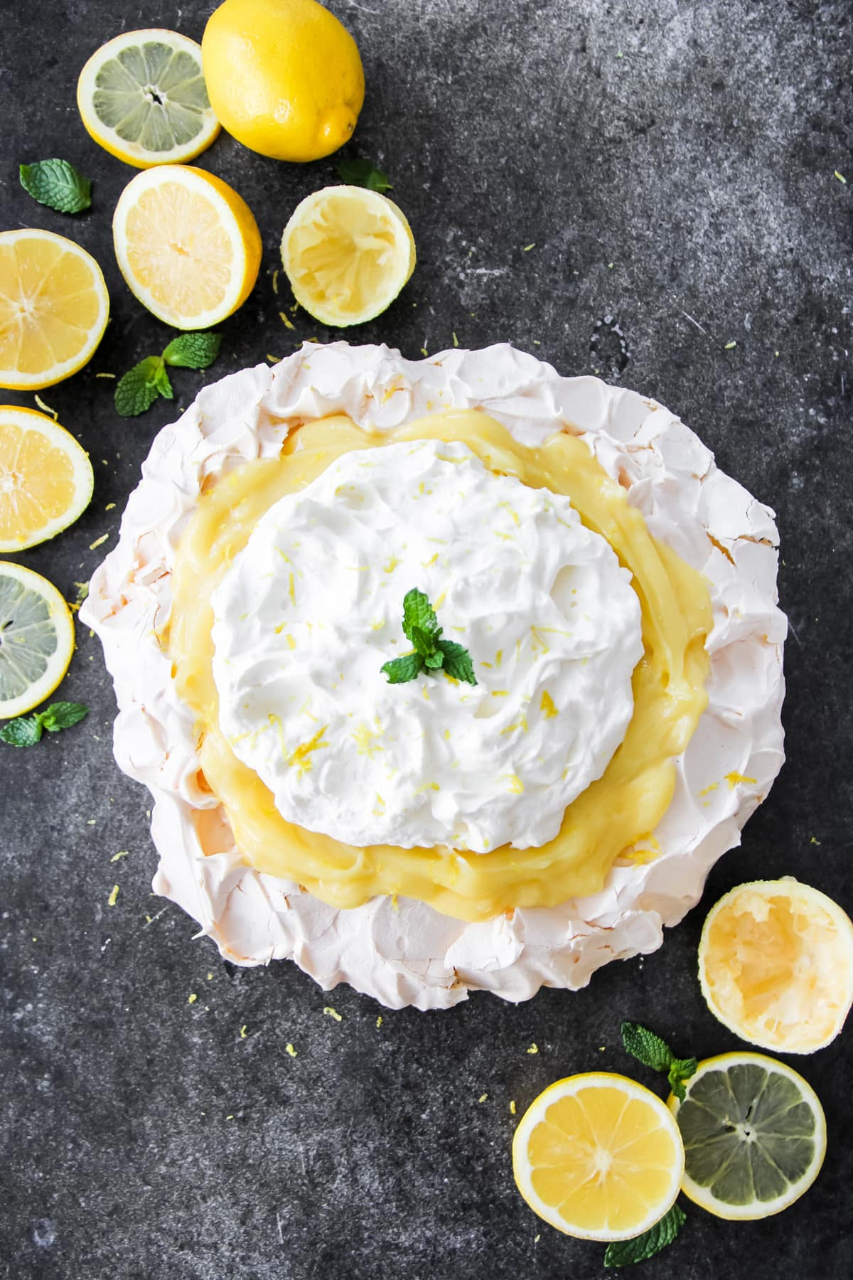 a top down view of a lemon pavlova with lemon curd and whipped cream. in the background are sliced lemons and sprigs of mint