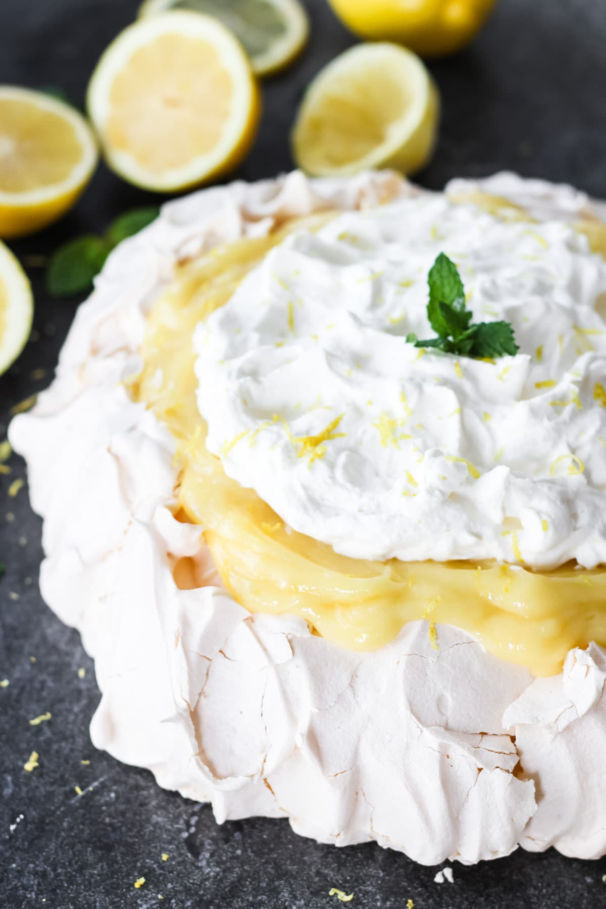 a side view of a lemon pavlova with lemon curd and whipped cream. in the background are sliced lemons